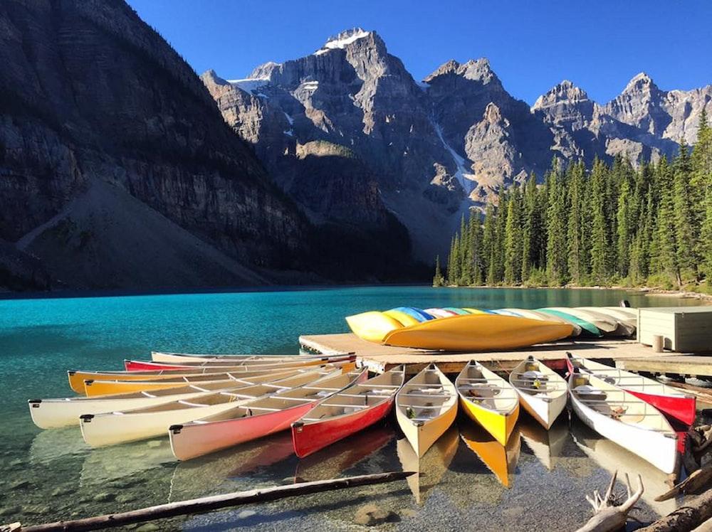 canoe beside dock on body of water