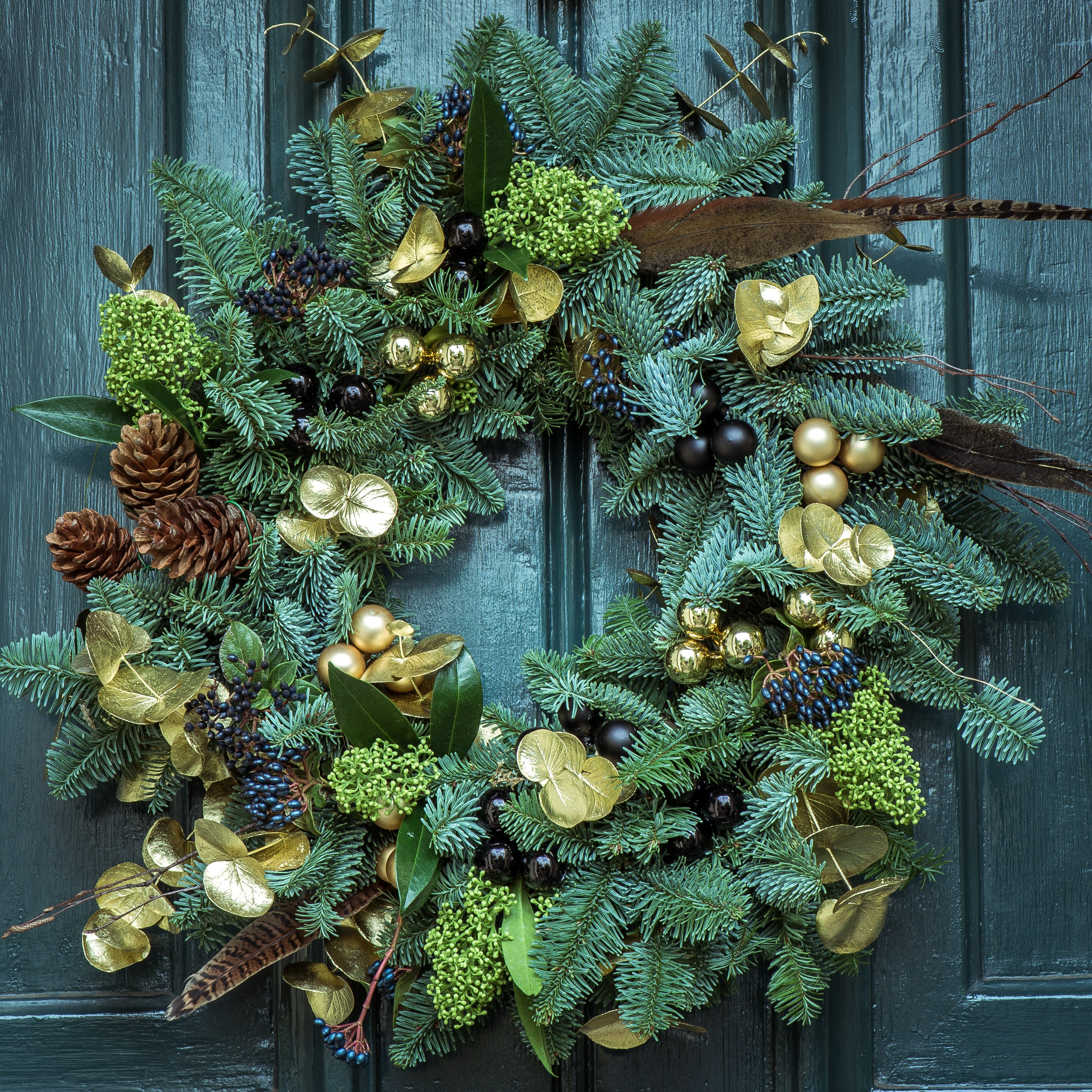 A green wreath on a wooden door.