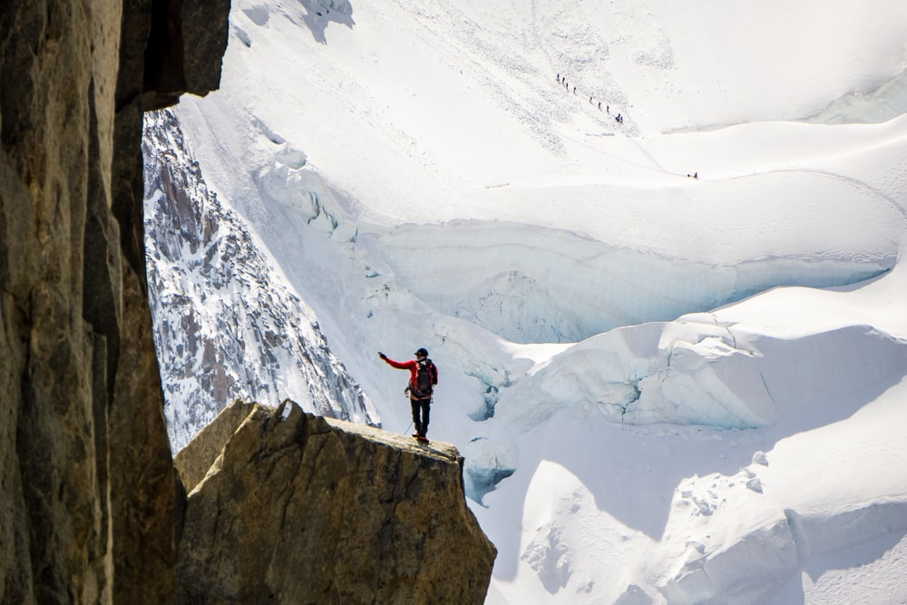 person standing on top of mountain beside snow mountian