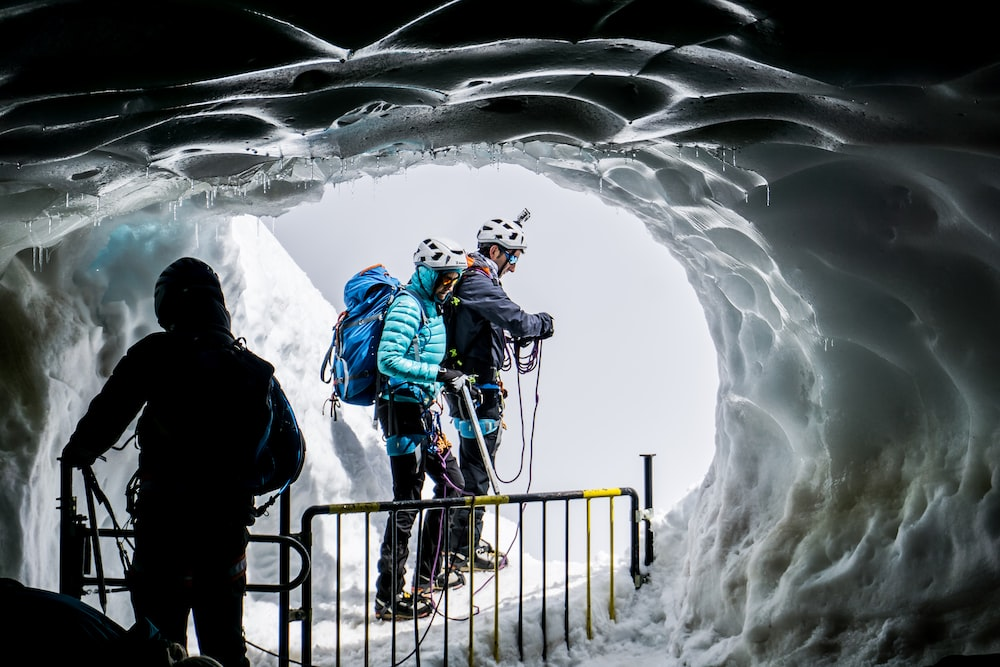 people walking on ice covered cave