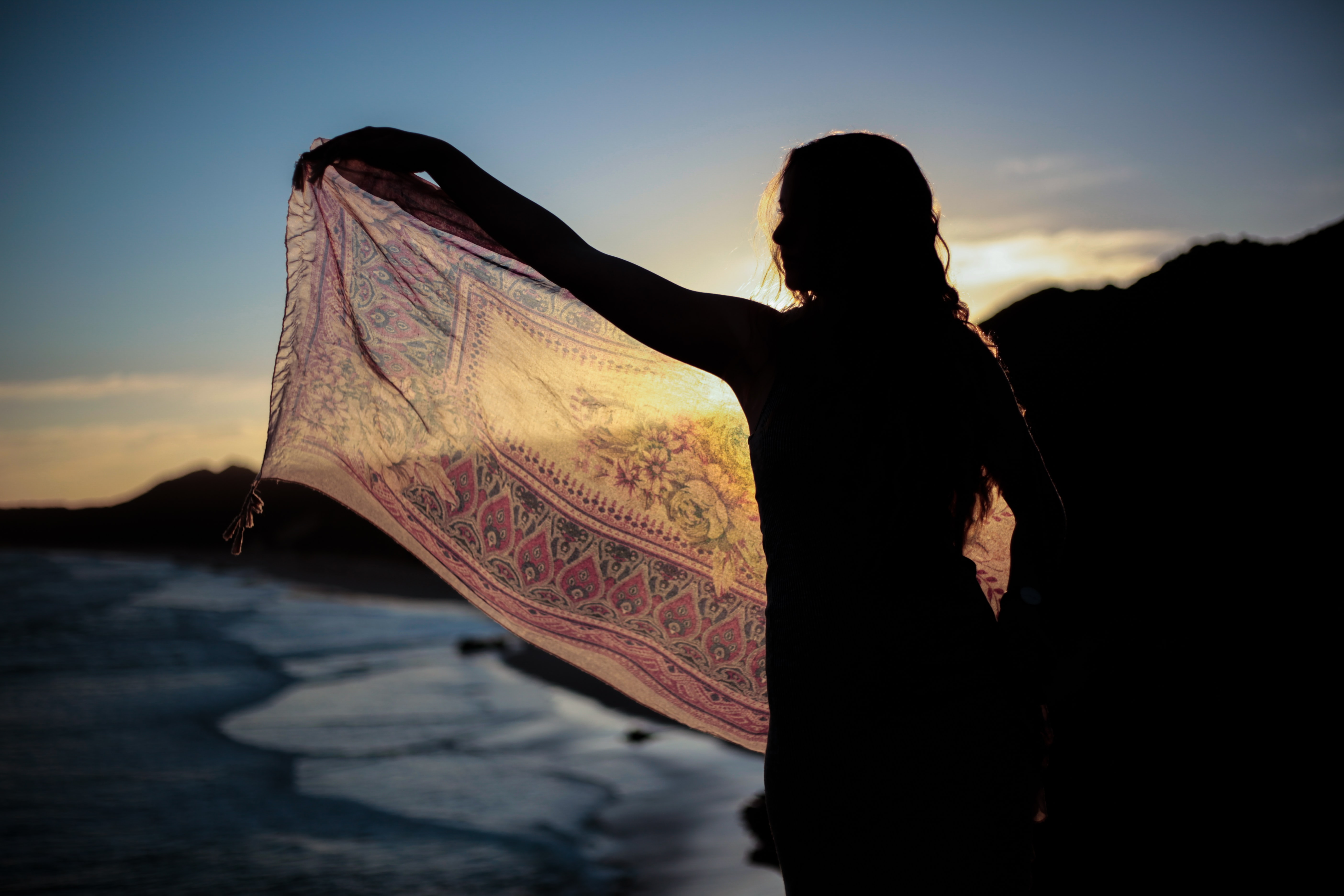 silhouette of woman holding scarf
