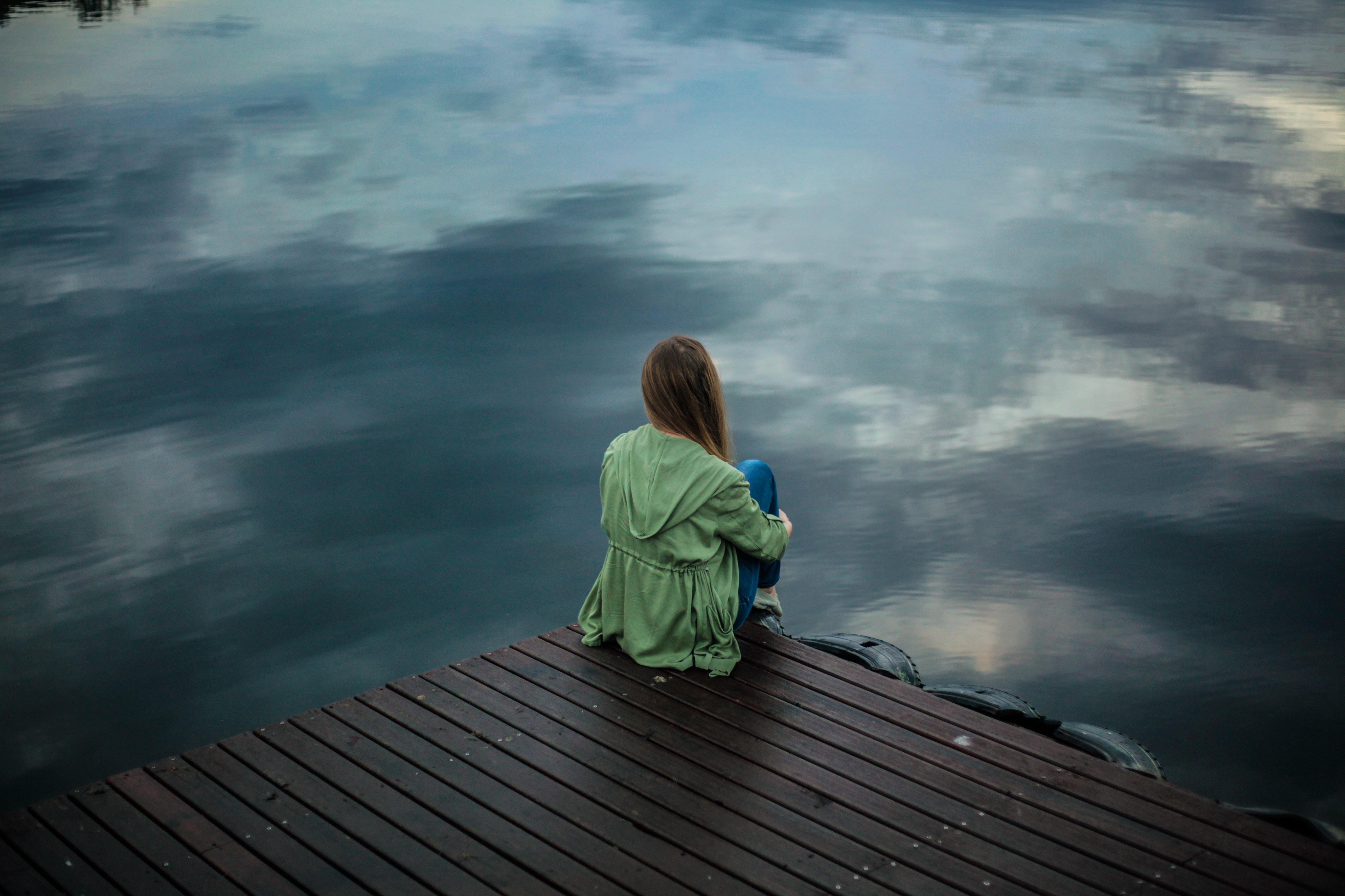 woman sitting on dock near body of water
