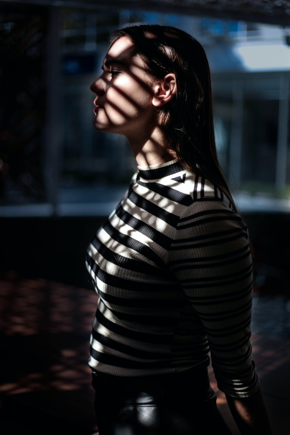 A sad woman in a striped shirt.