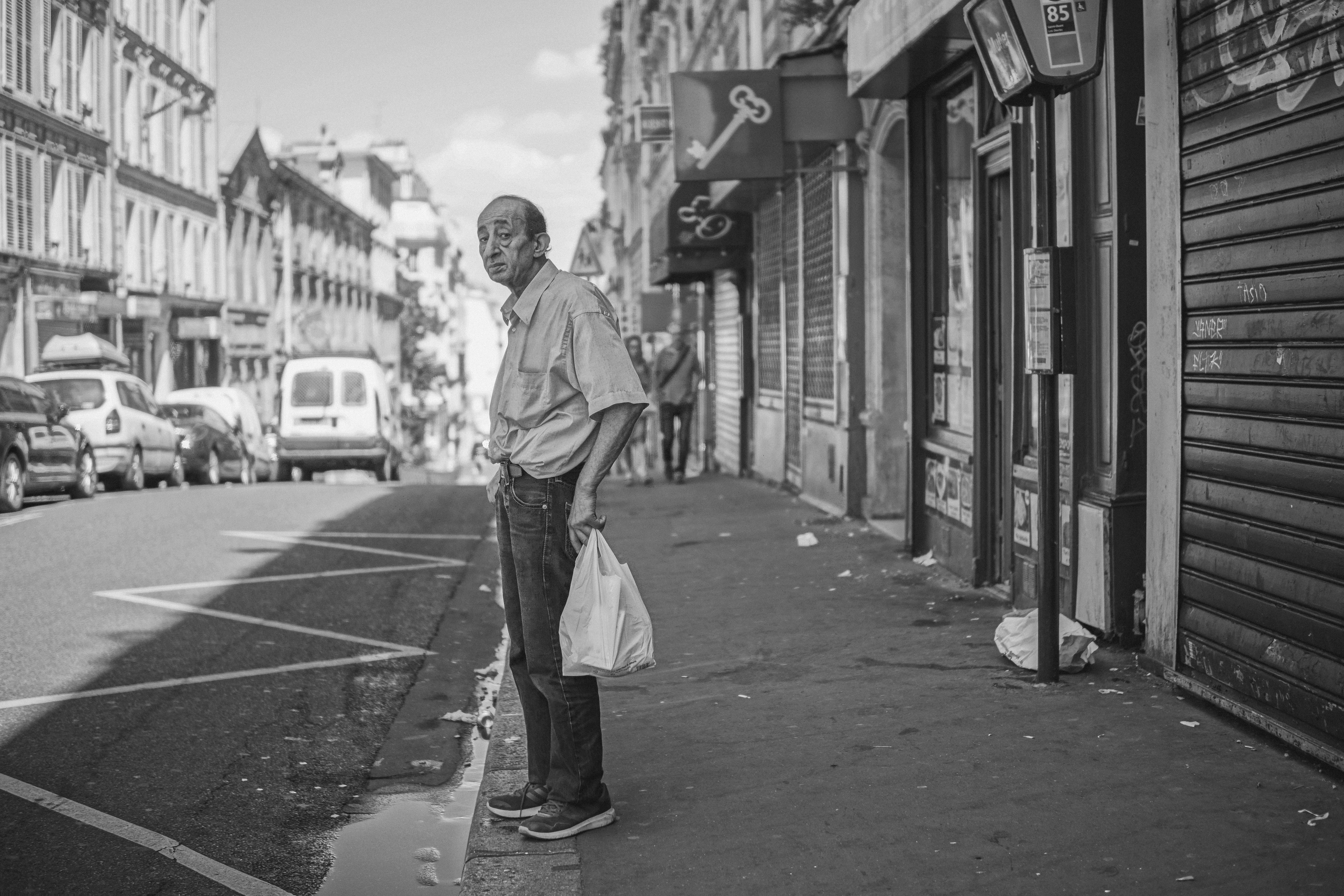grayscale photography of man standing on stret
