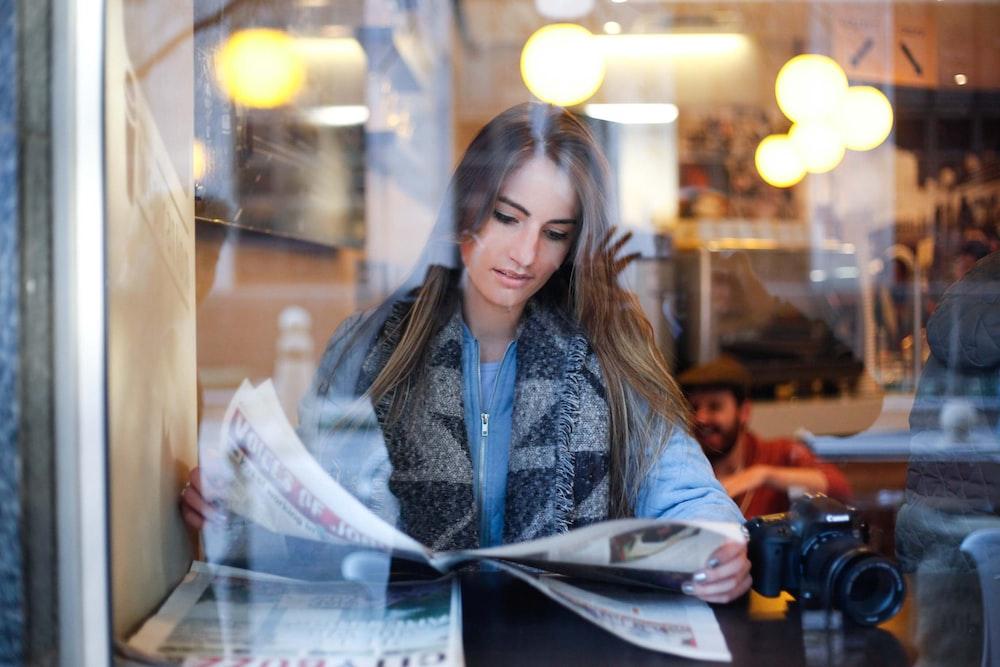 woman reading newspaper near black DSLR camera