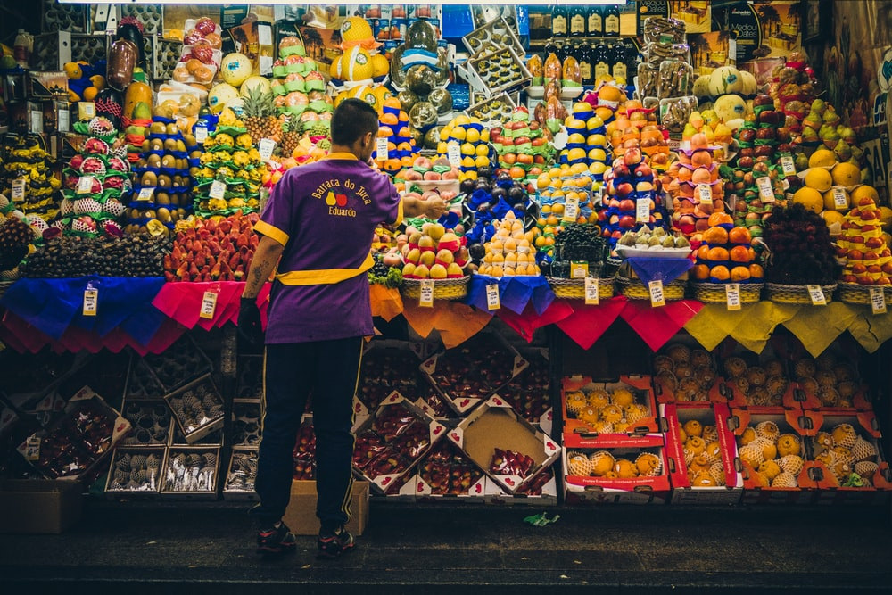 man standing in front of produce stand