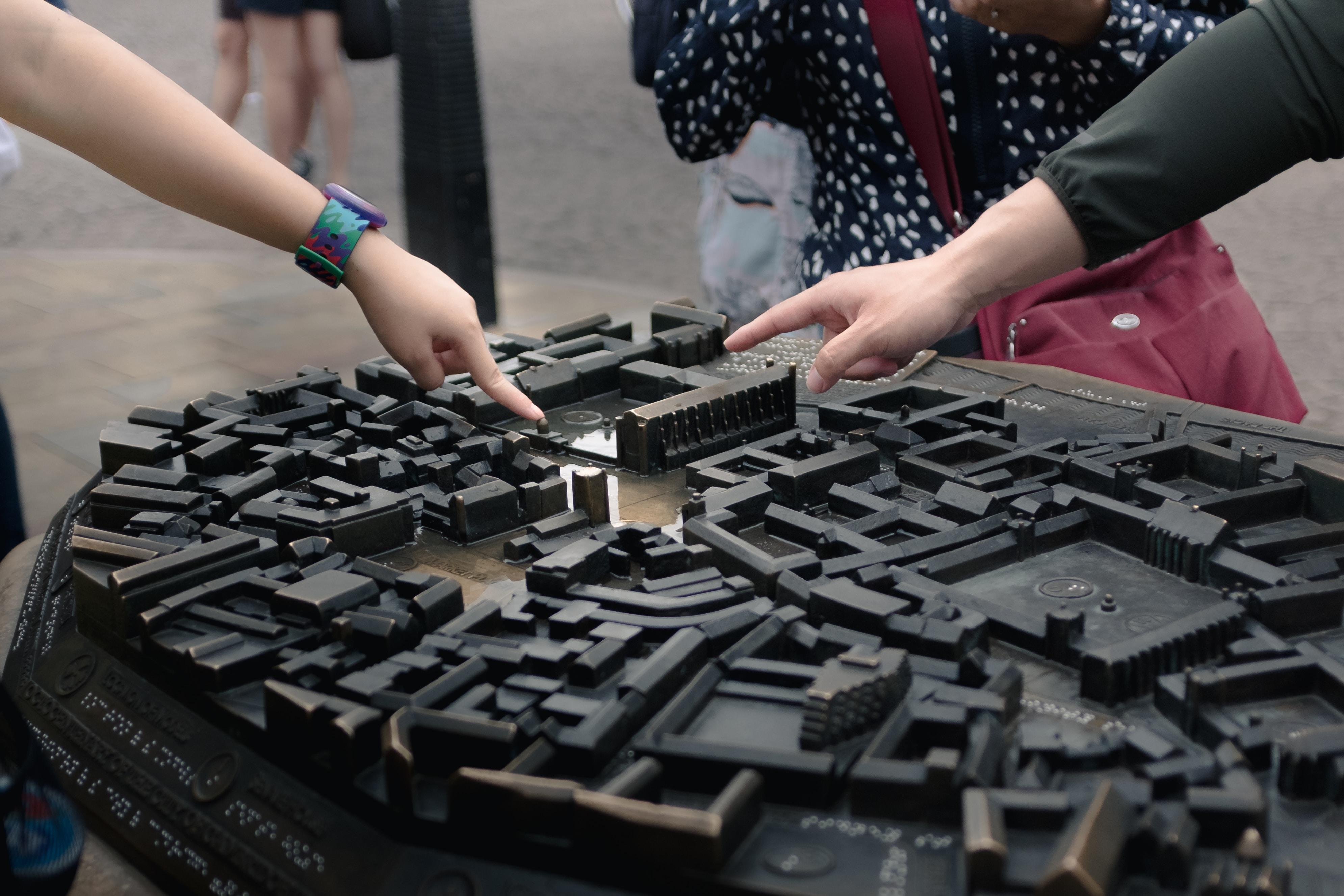 people holding black building bricks