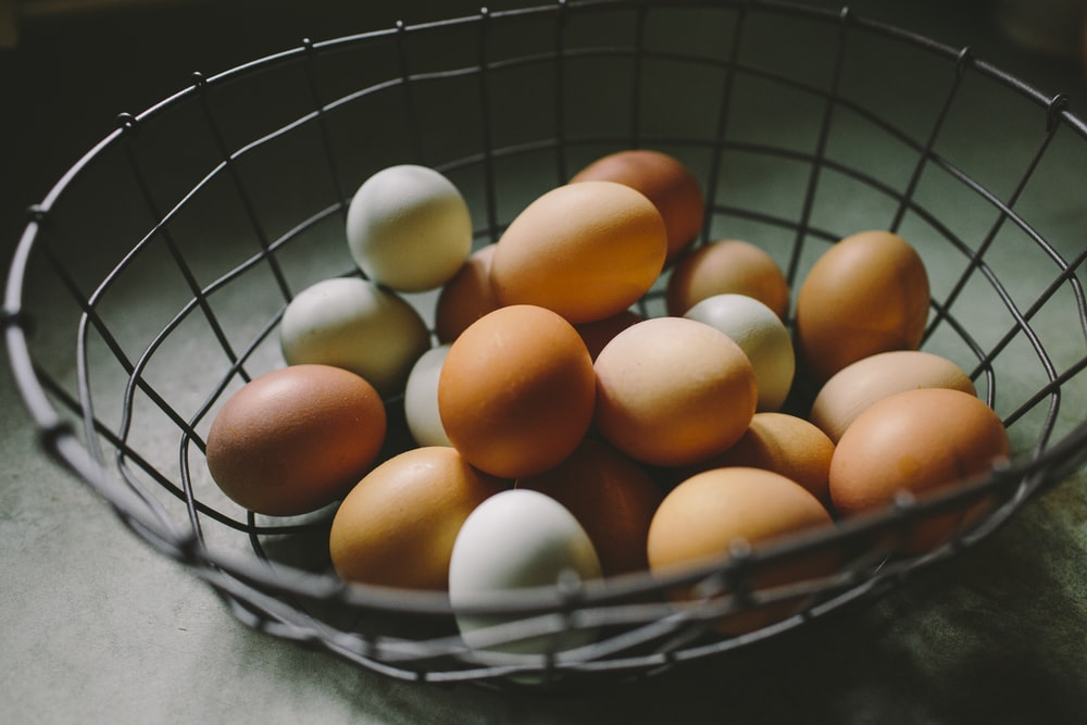 brown and white eggs on gray basket