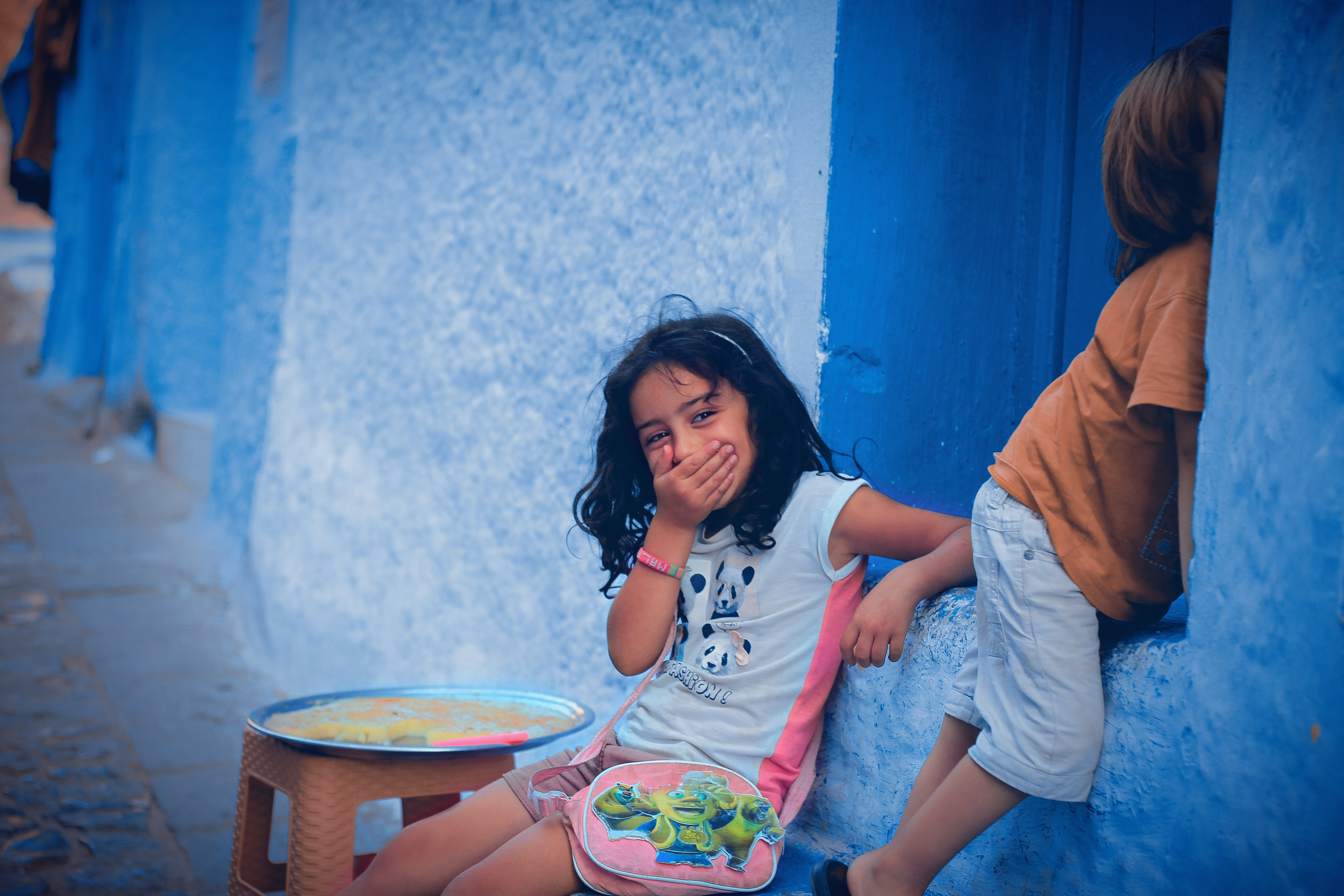 two children leaning on blue wall