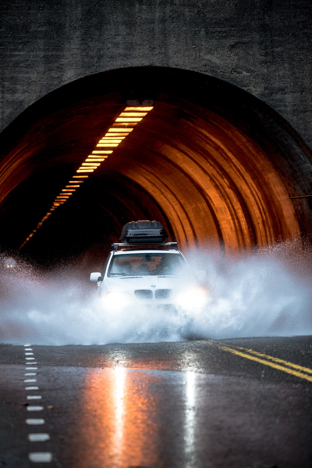 white BMW car crossing asphalt road in front of concrete tunnel