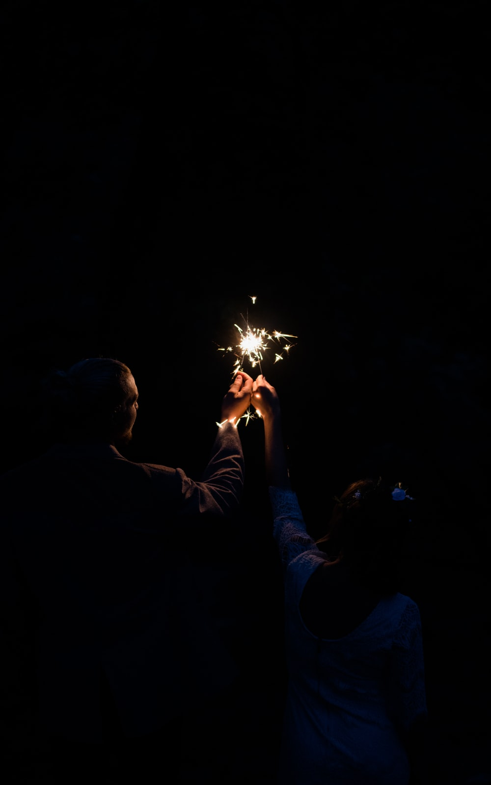 man and woman holding firecracker at nighttime
