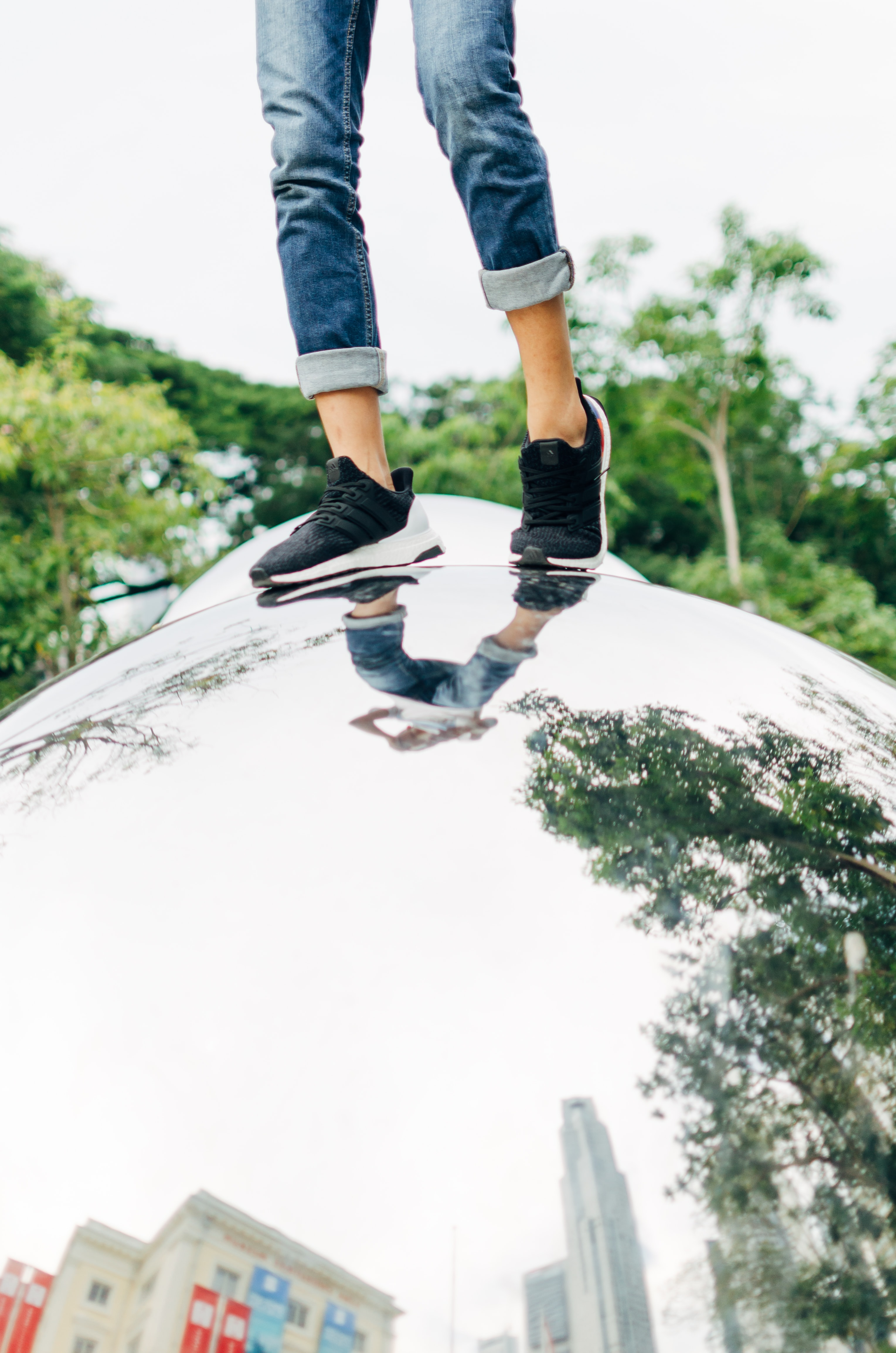 person wearing shoes and pants standing on chrome structure at daytime