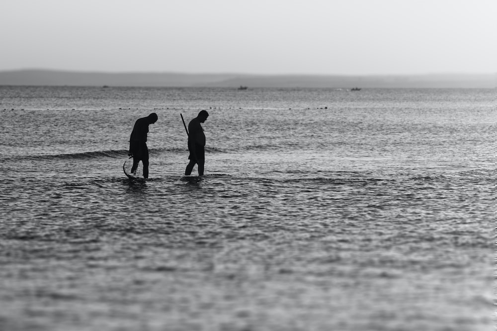 silhouette of two man on body of water