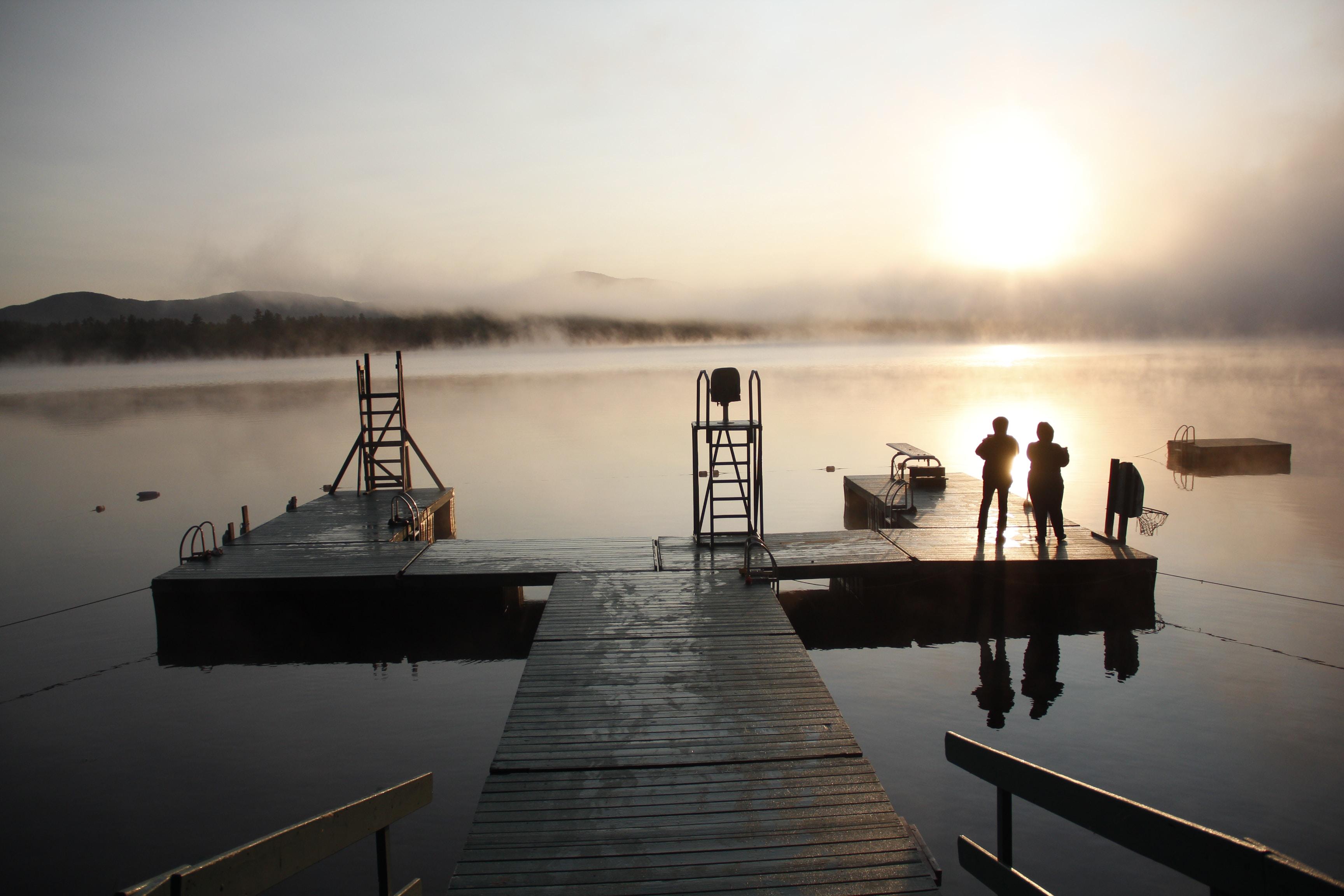 three people on wooden dock under the sun
