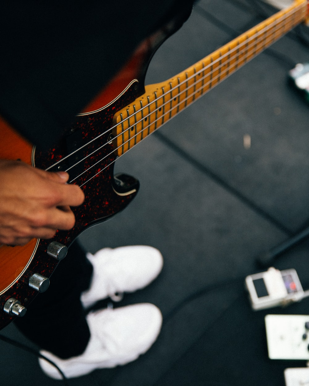 person playing brown and black bass guitar