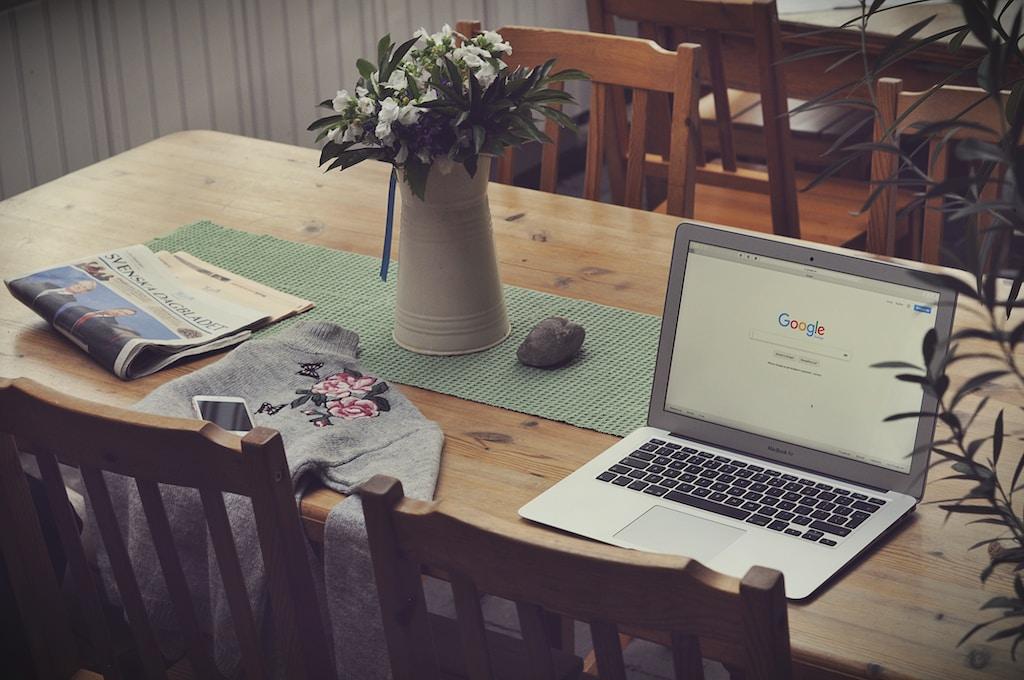 laptop on top of table beside vase of flowers