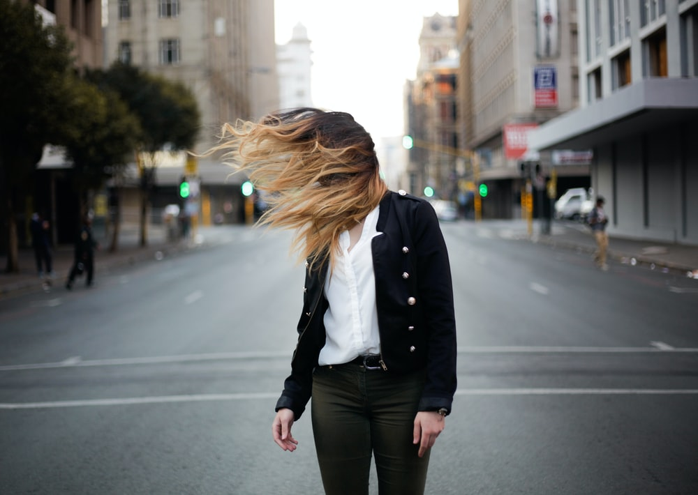 woman waving hair by the wind on road