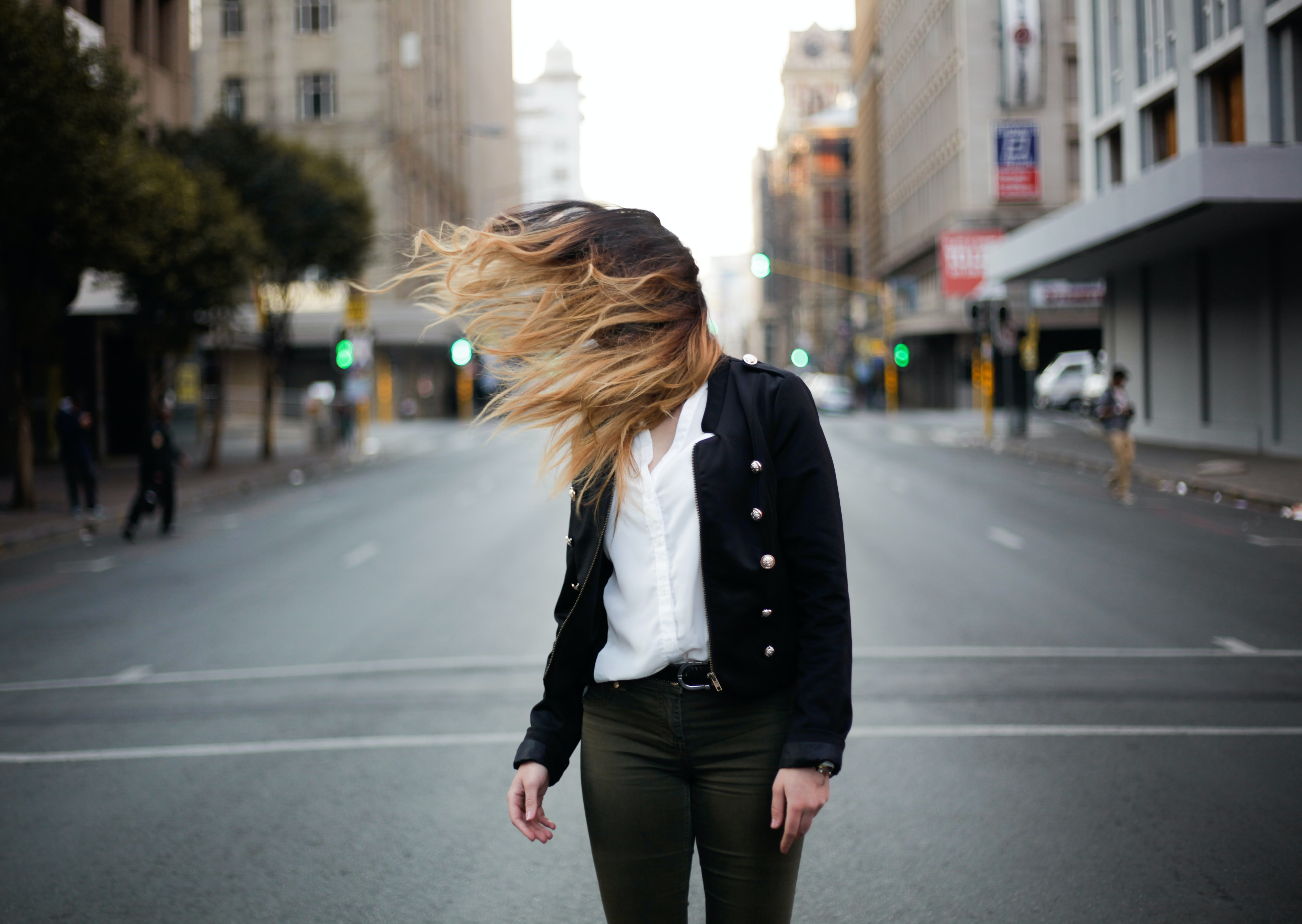 A woman turning her head in the middle of the street and covering her face with her hair.