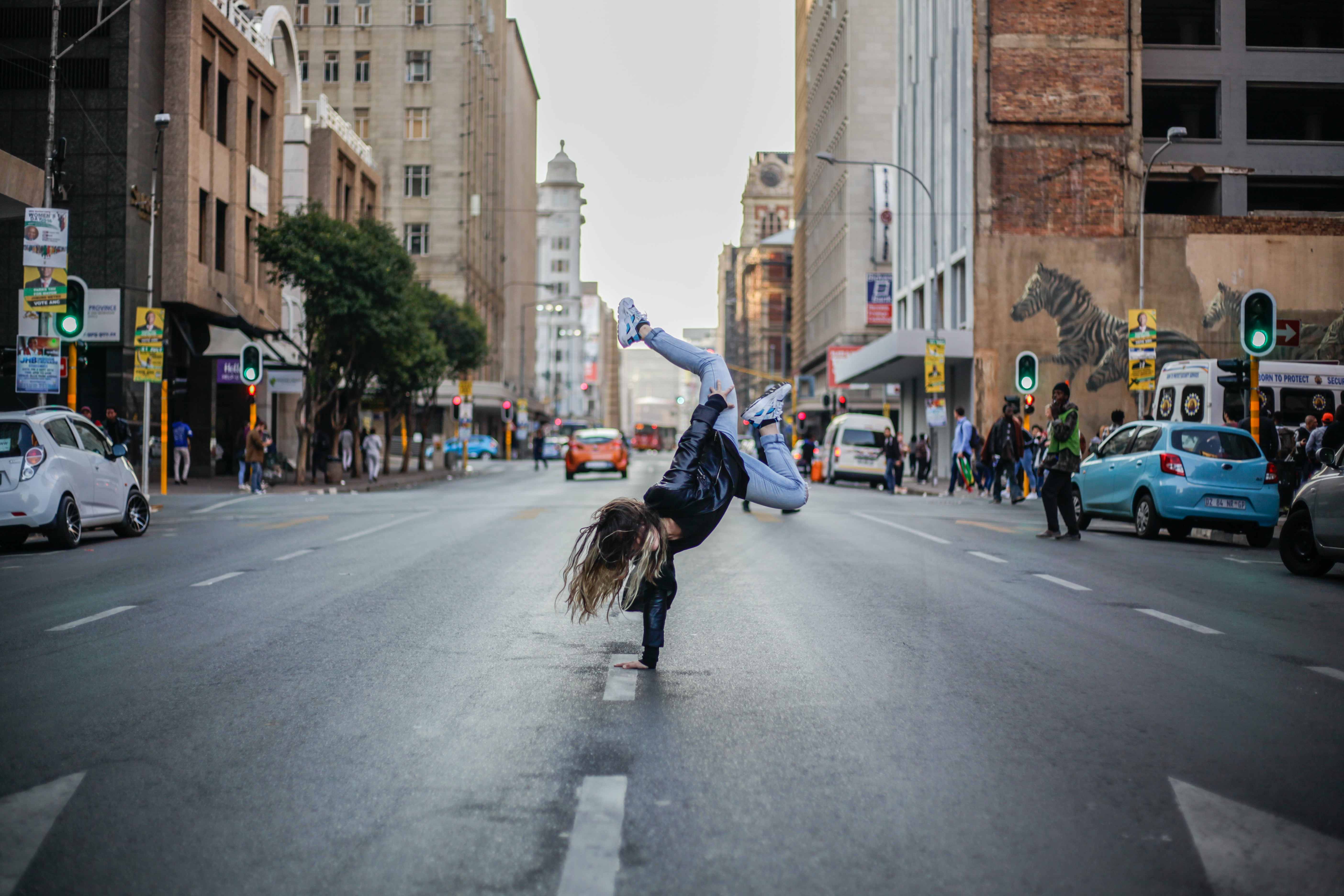 A woman doing a single handed handstand in the middle of the street.