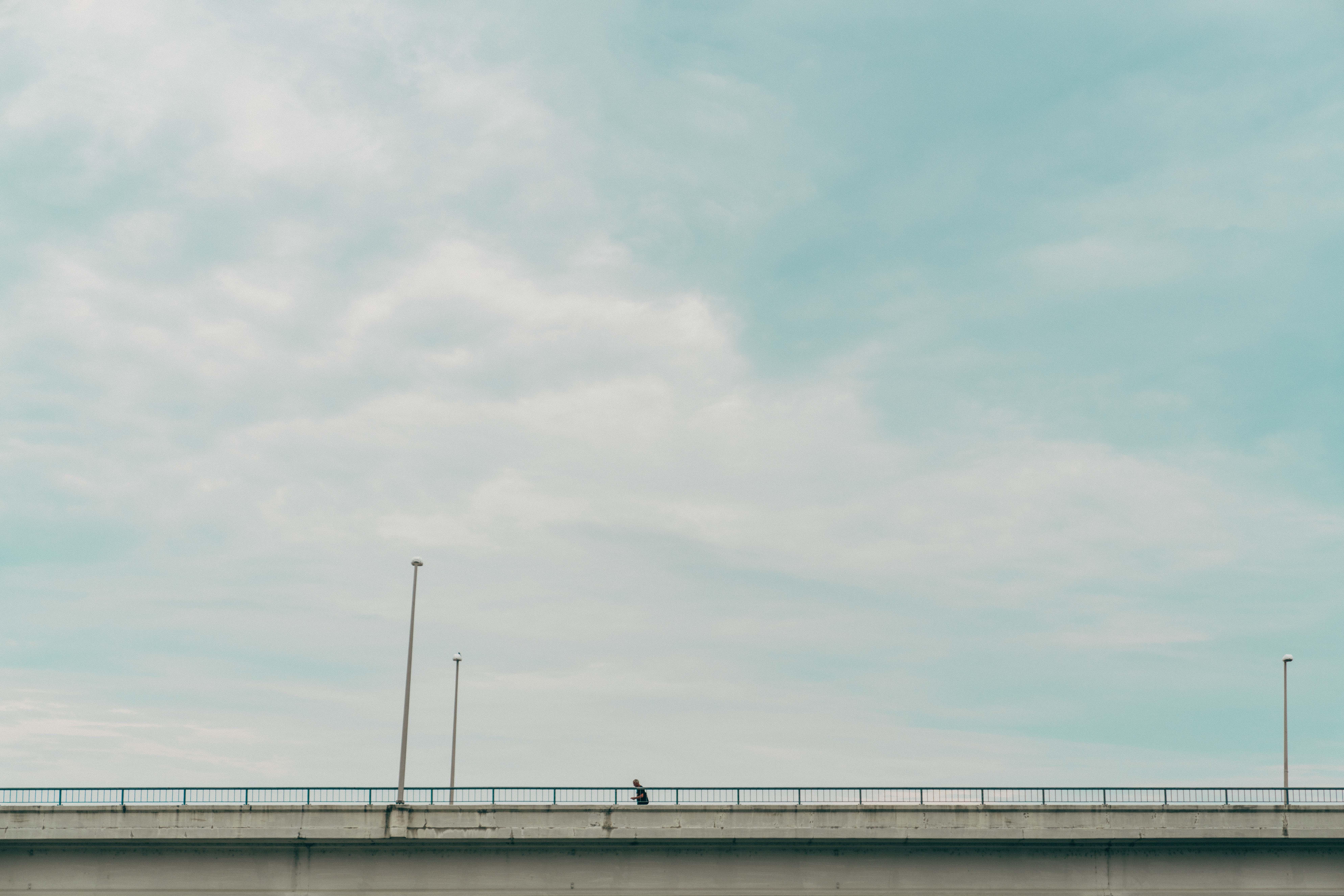 gray suspension bridge under white clouds during daytime