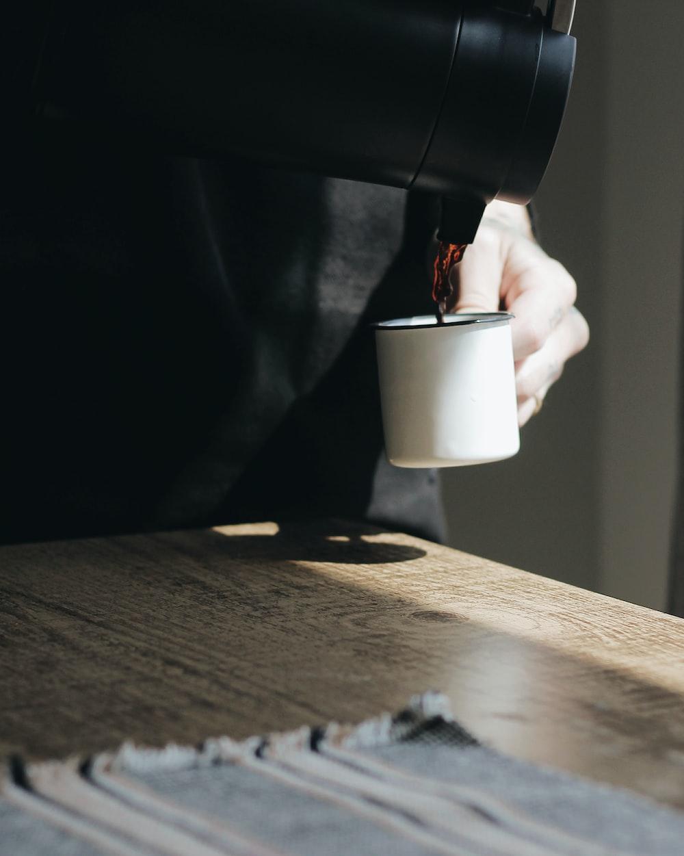 person pouring tea on mug