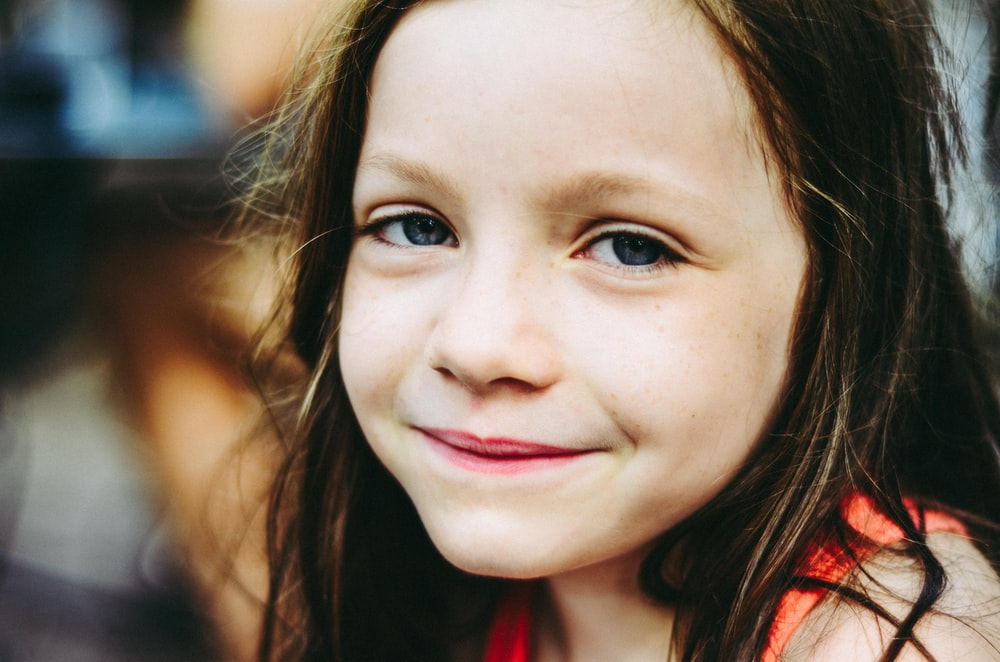 selective focus photography of girl smiling while taking photo
