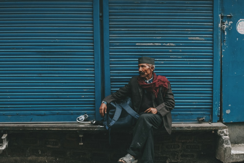 man sitting on gray bench in front of blue shutter door