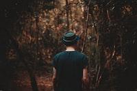 man wearing black hat walking on forest during daytime