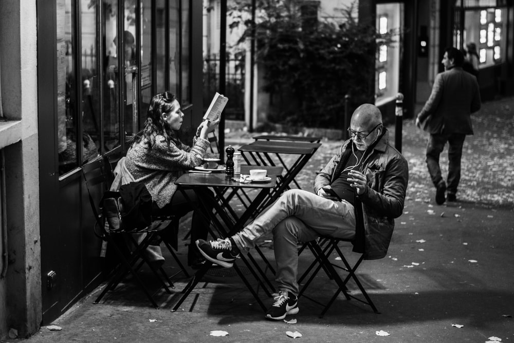 grayscale photo of man and woman sitting beside table holding smartphones