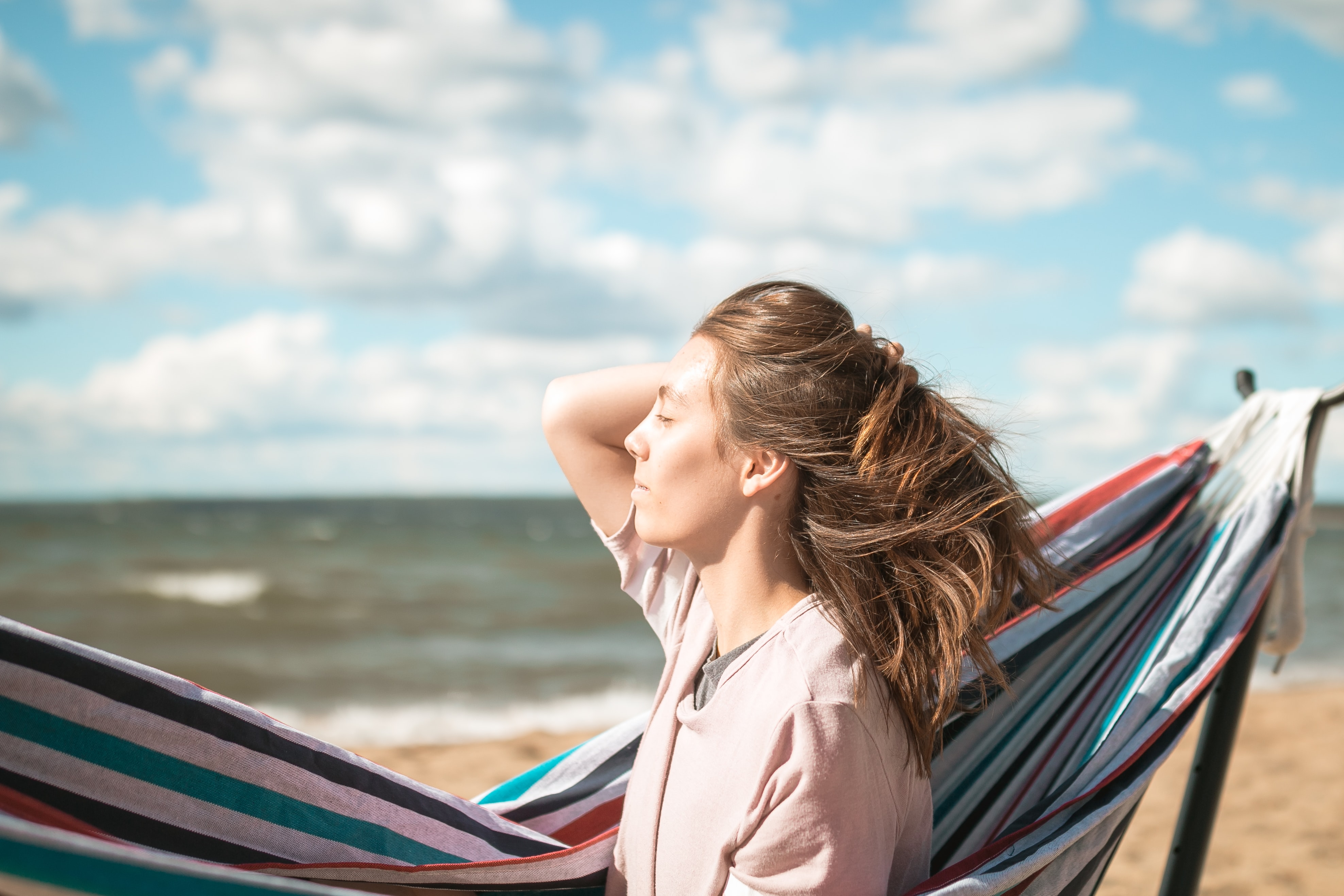 woman holding her hair backwards while sitting beside portable hammock on seashore during daytime