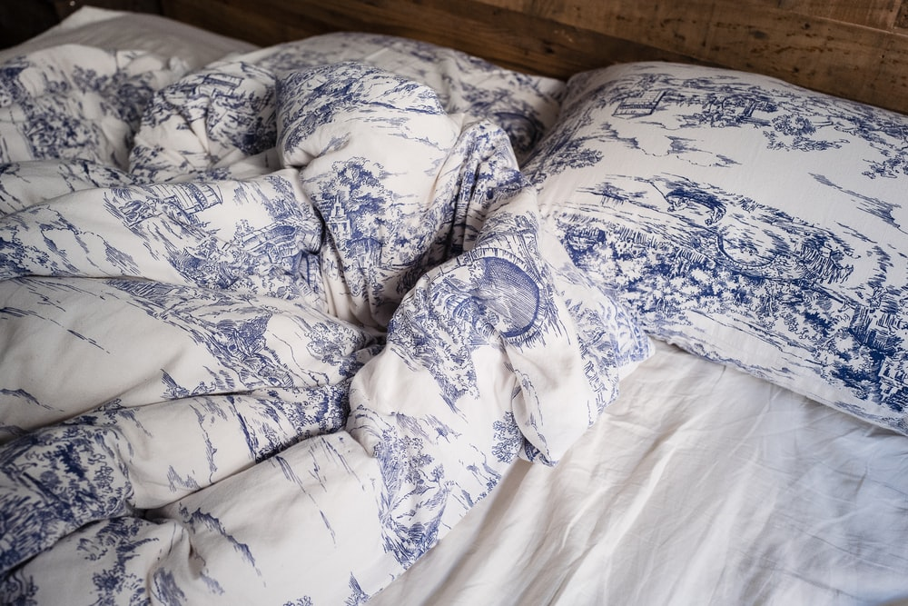 blue and white pillow on white bed