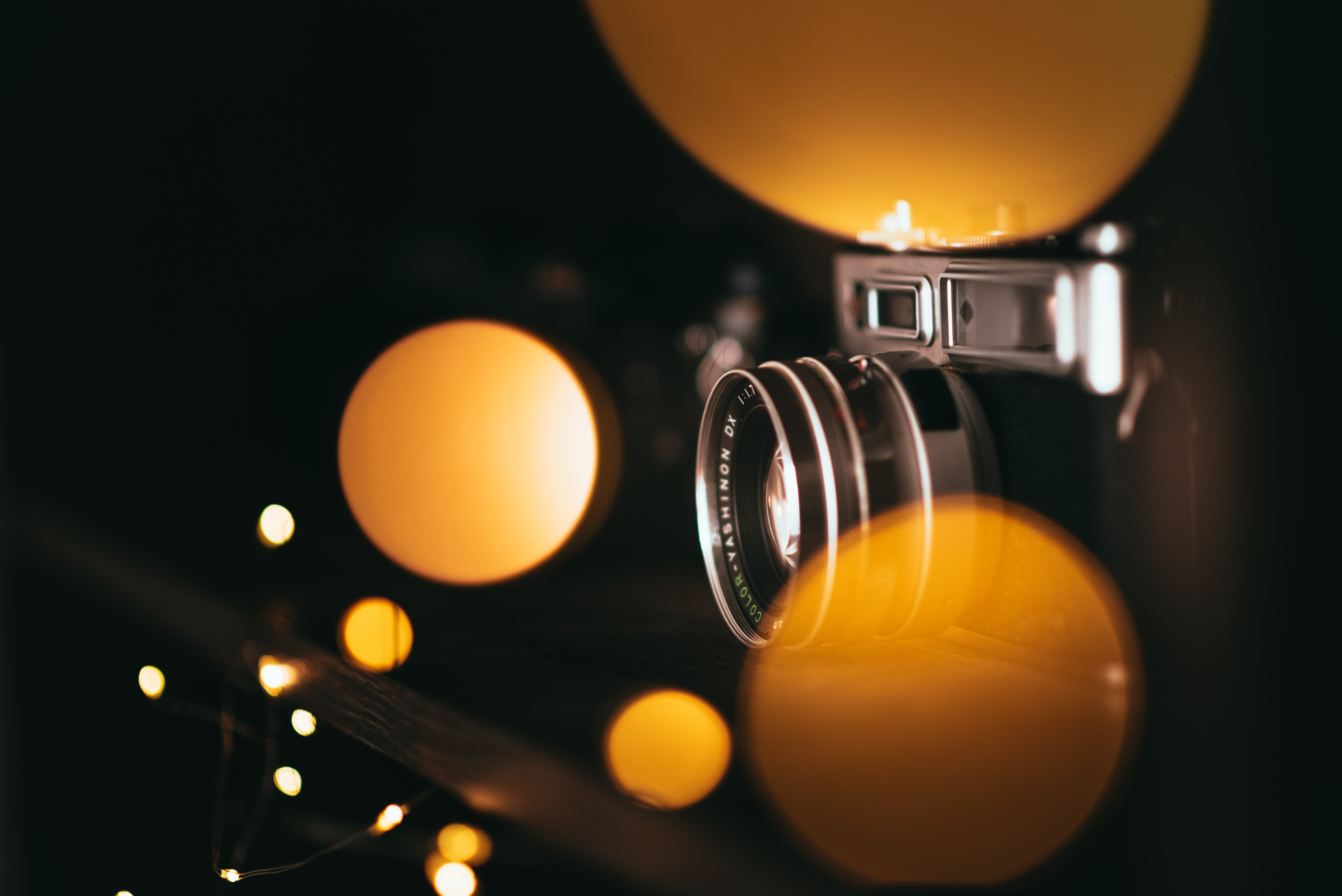 black and gray SLR camera with yellow bokeh light