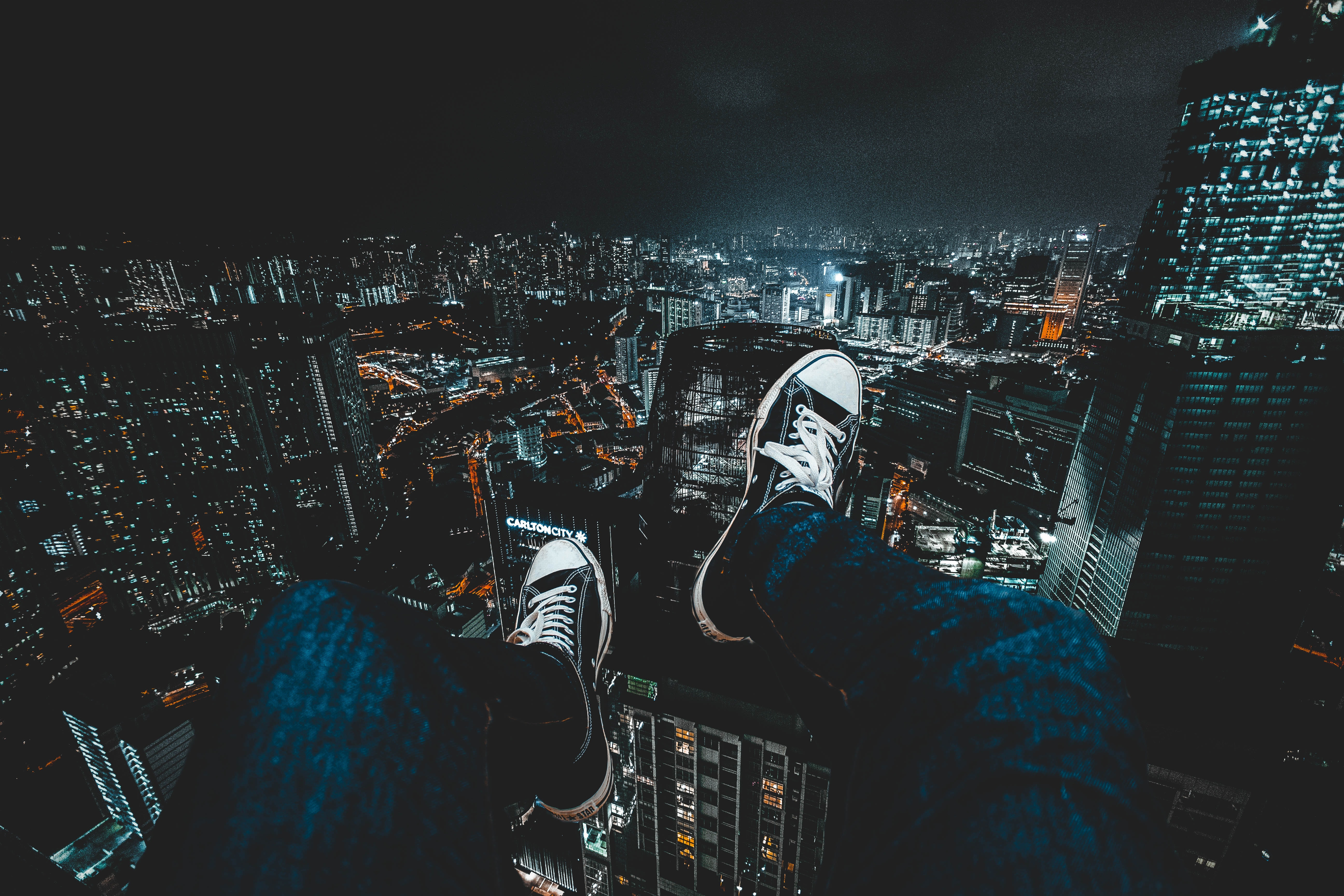 person wearing blue jeans facing cityscape during nighttime