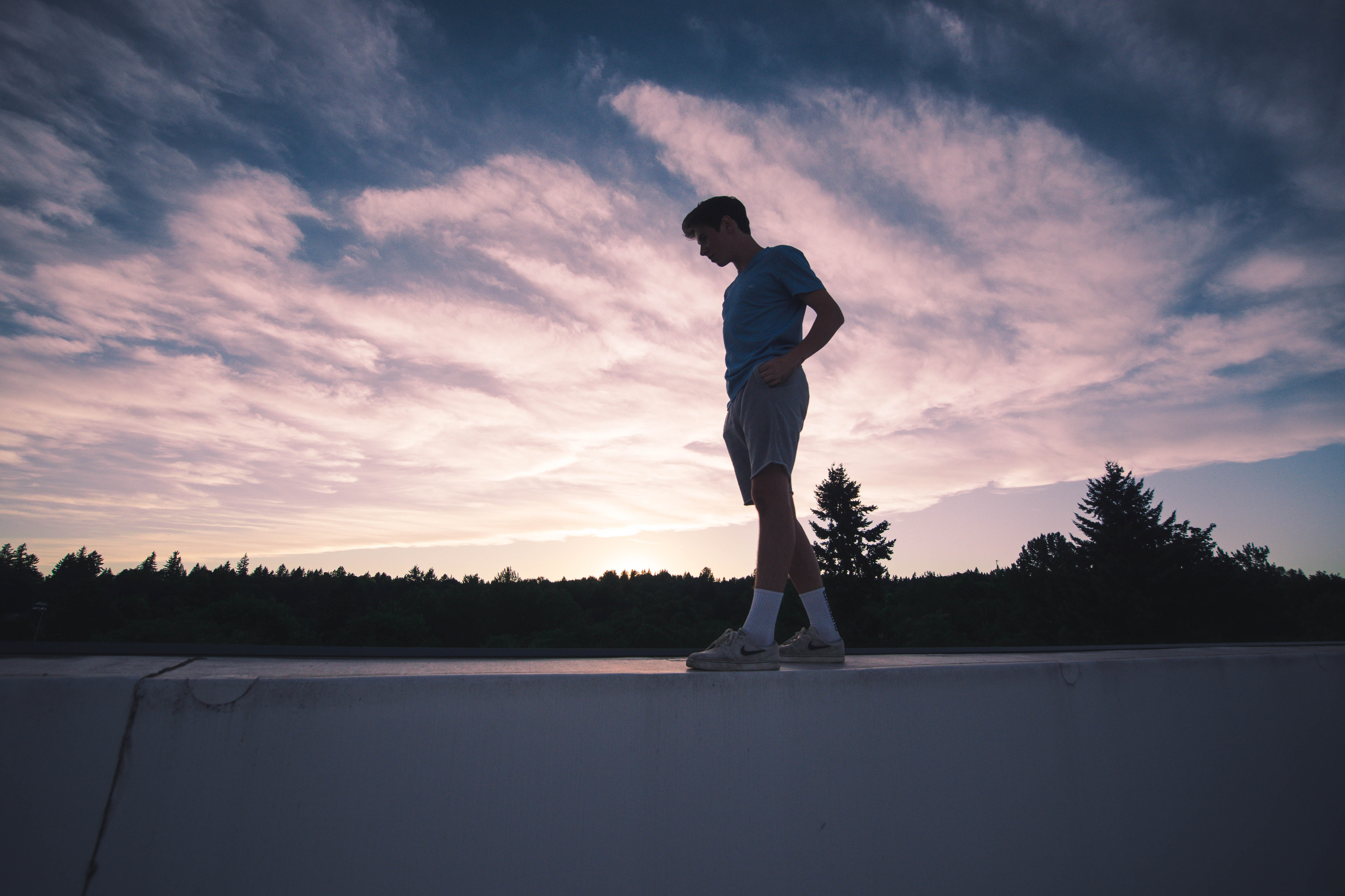man standing on white concrete ledge below cloudy sky during dawn