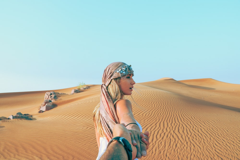 man and woman holding hands while in desert
