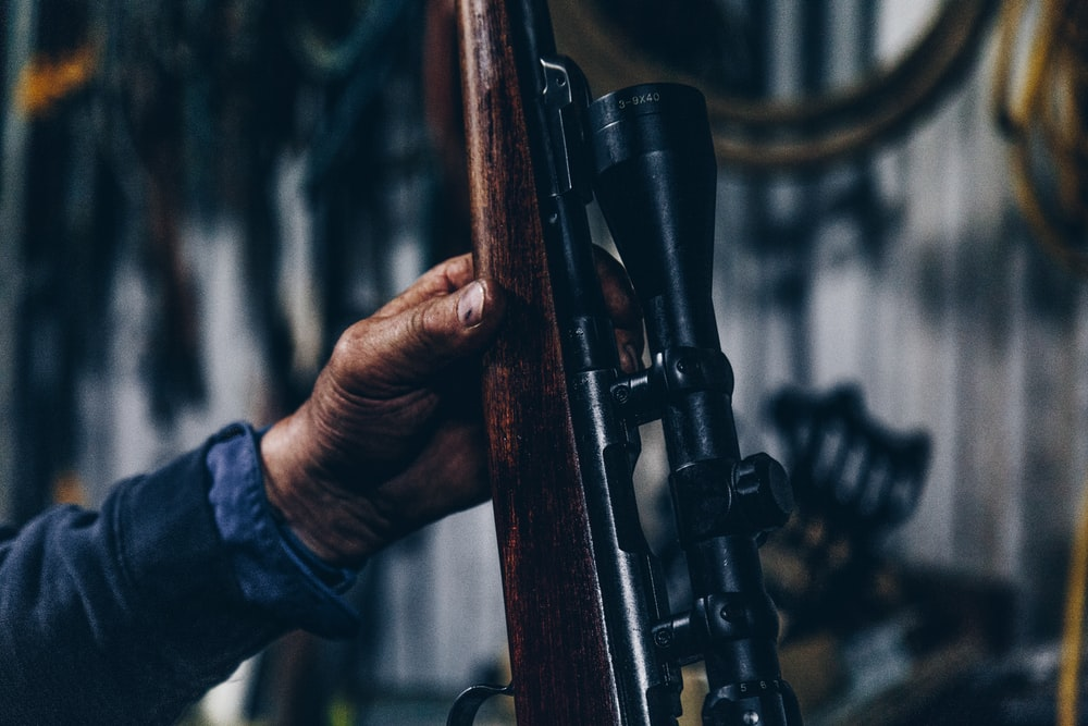 person holding brown and black hunting rifle
