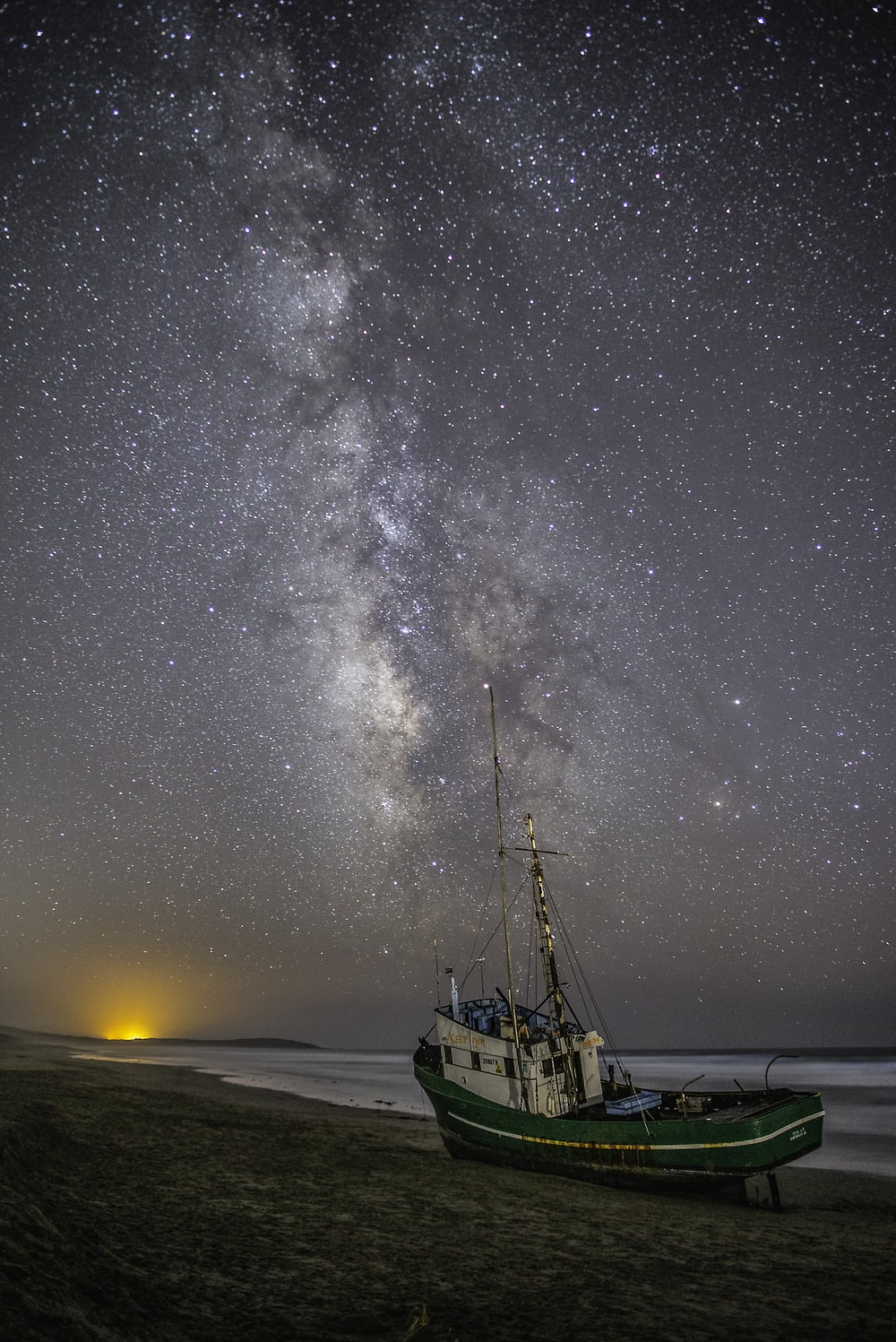 green and white fishing boat on gray sand under white and gray sky