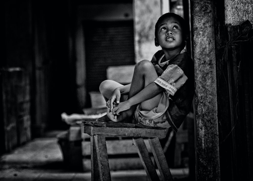 grayscale photo of boy sitting on wooden bench beside wall while looking up