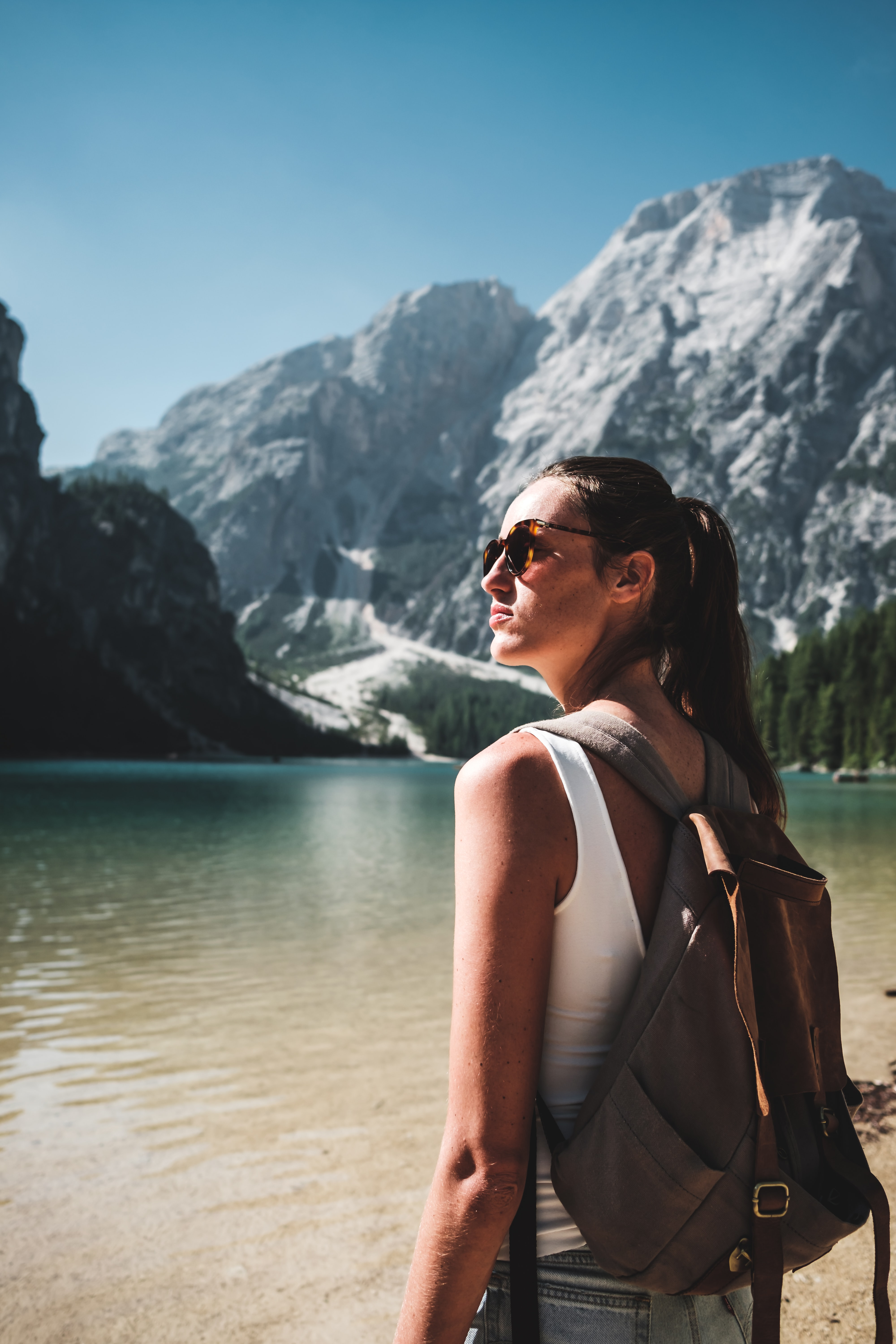 photo of woman wearing white tank top and gray backpack standing near body of water