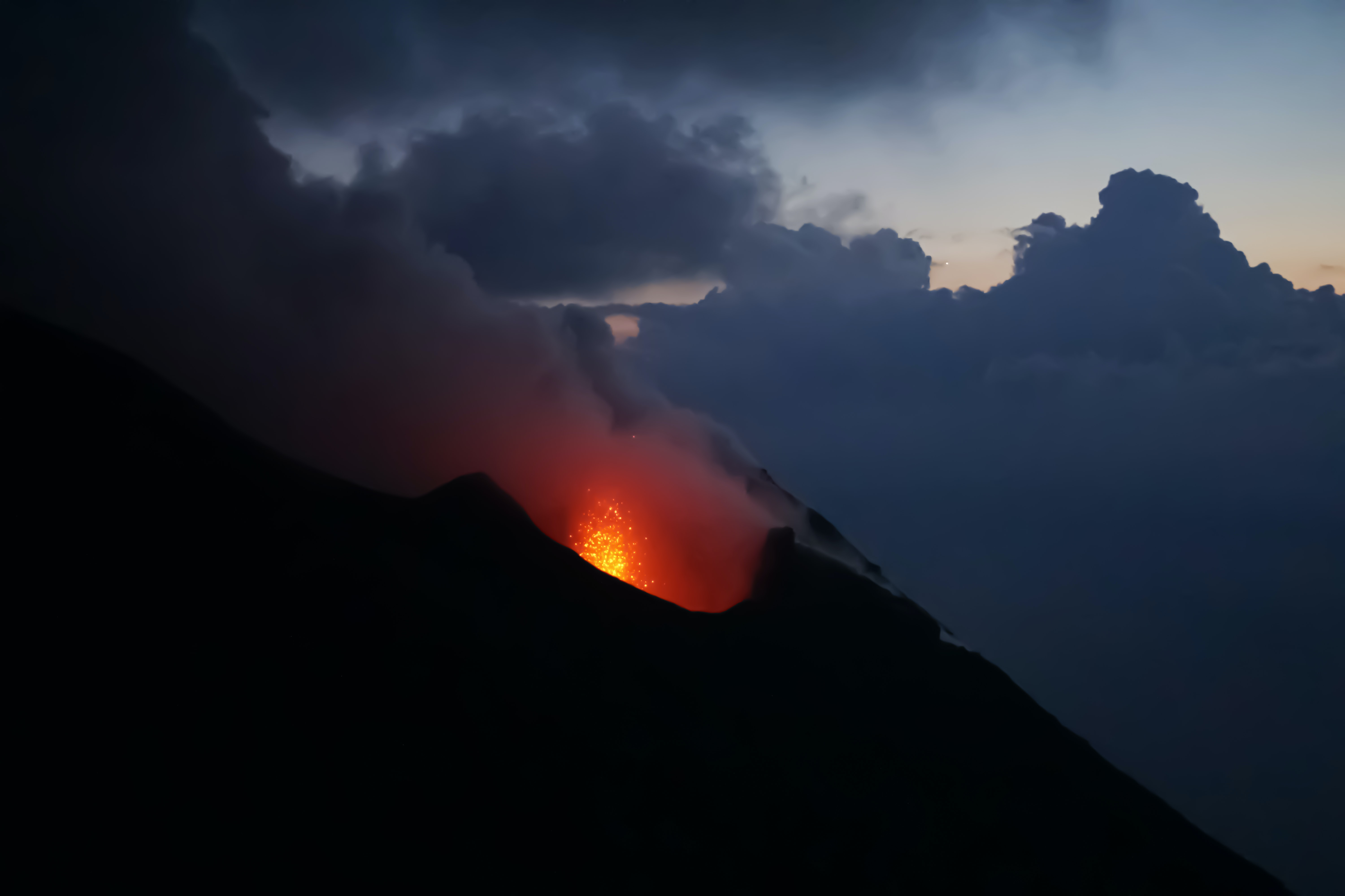 volcano with lava during black cloudy day