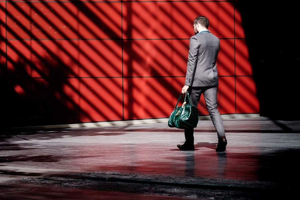 man holding green duffel bag while walking near red building at daytime