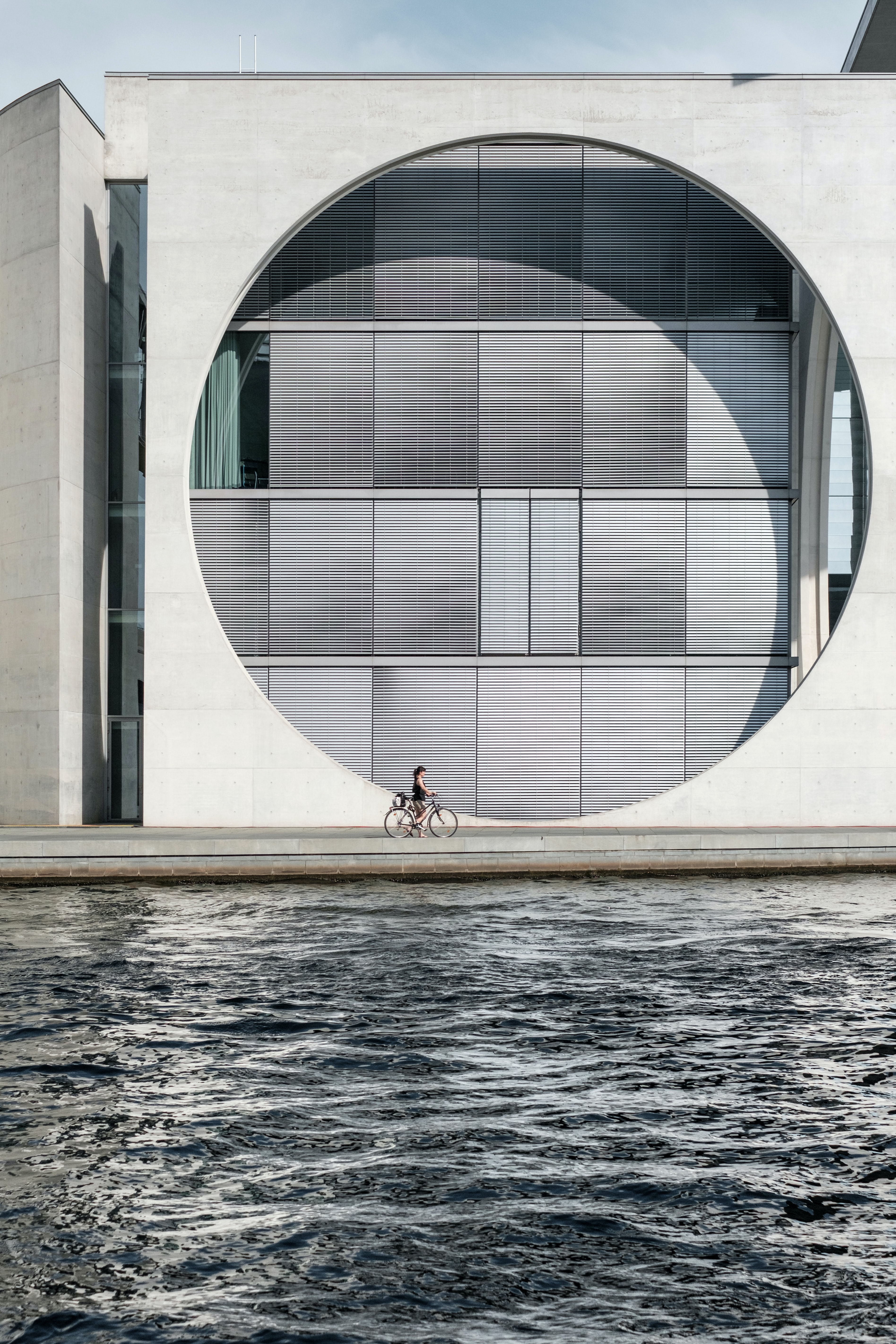 girl riding bike passing through body of water and building