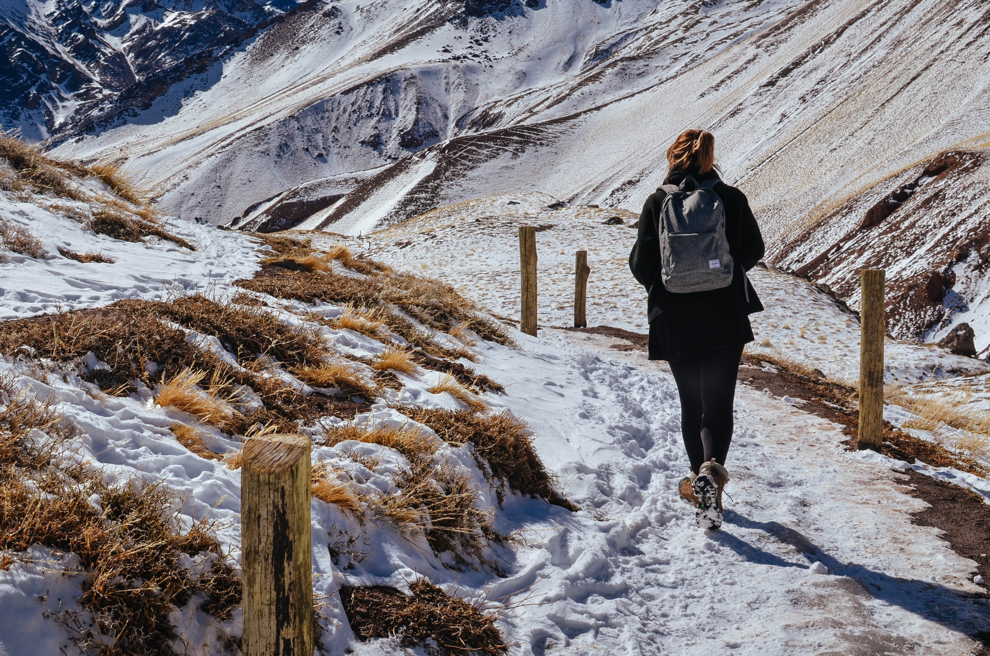 woman walking near mountain covered by snow during daytime
