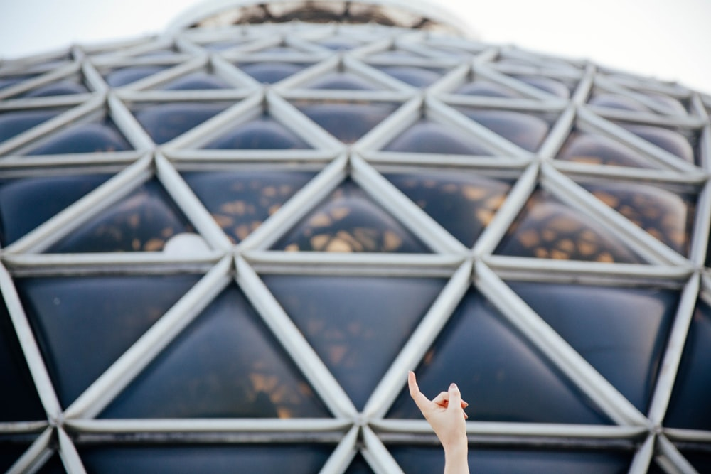 closeup photo of person pointing glass roof