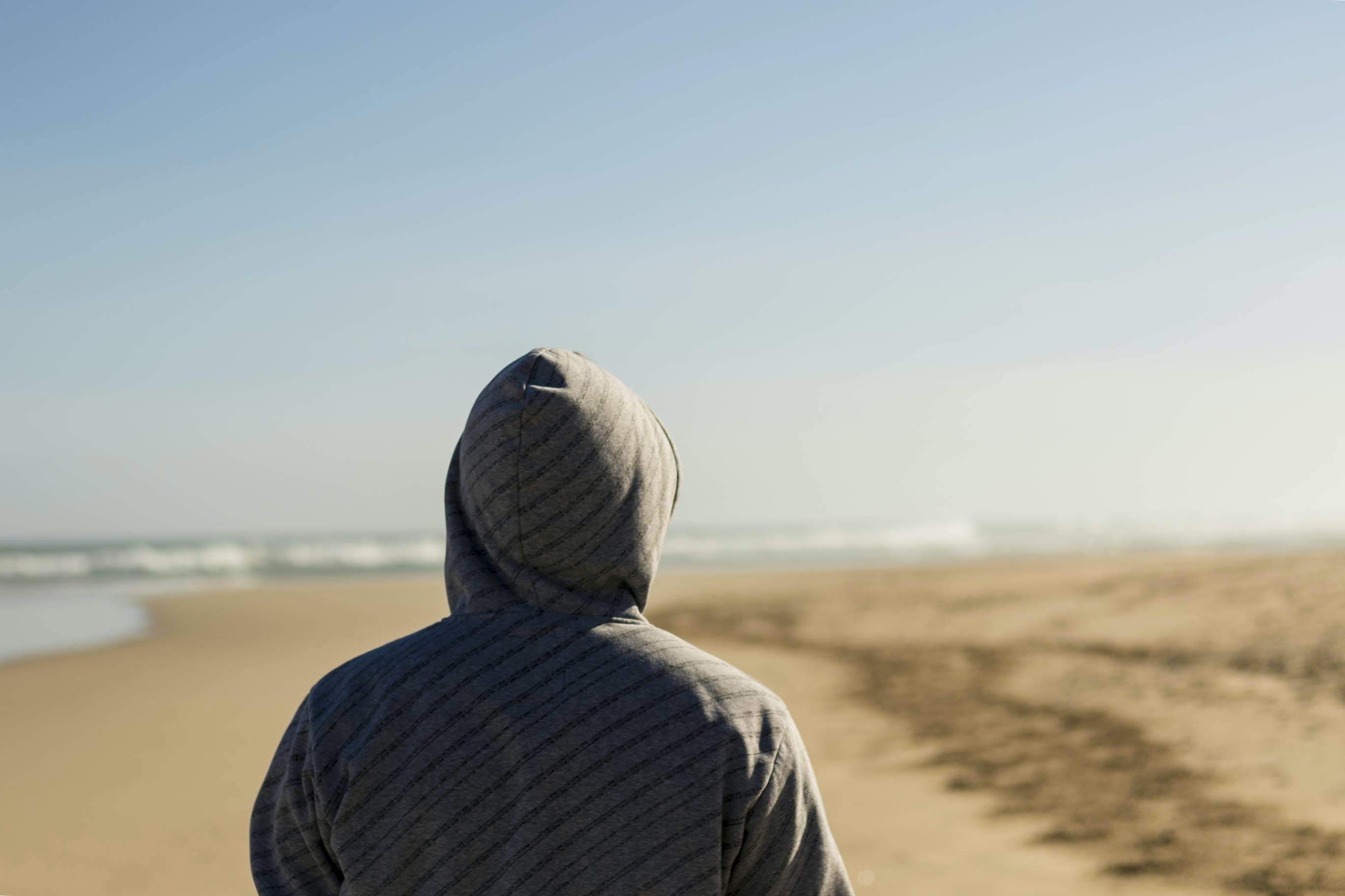 person wearing gray hooded top facing seashore