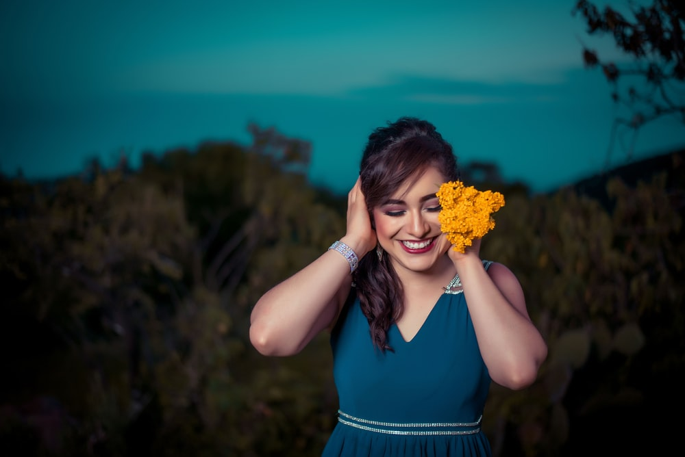 woman touching her hair while holding orange flowers