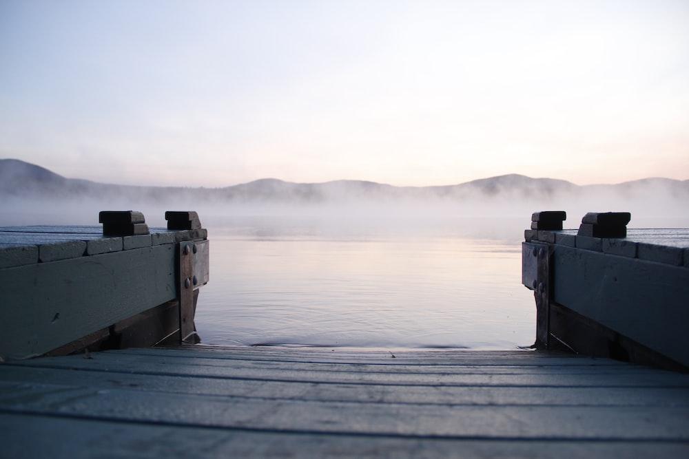 gray wooden dock near body of water