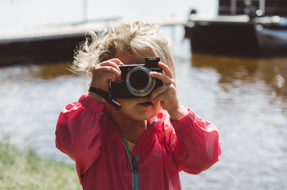 selective focus photography of girl using a camera