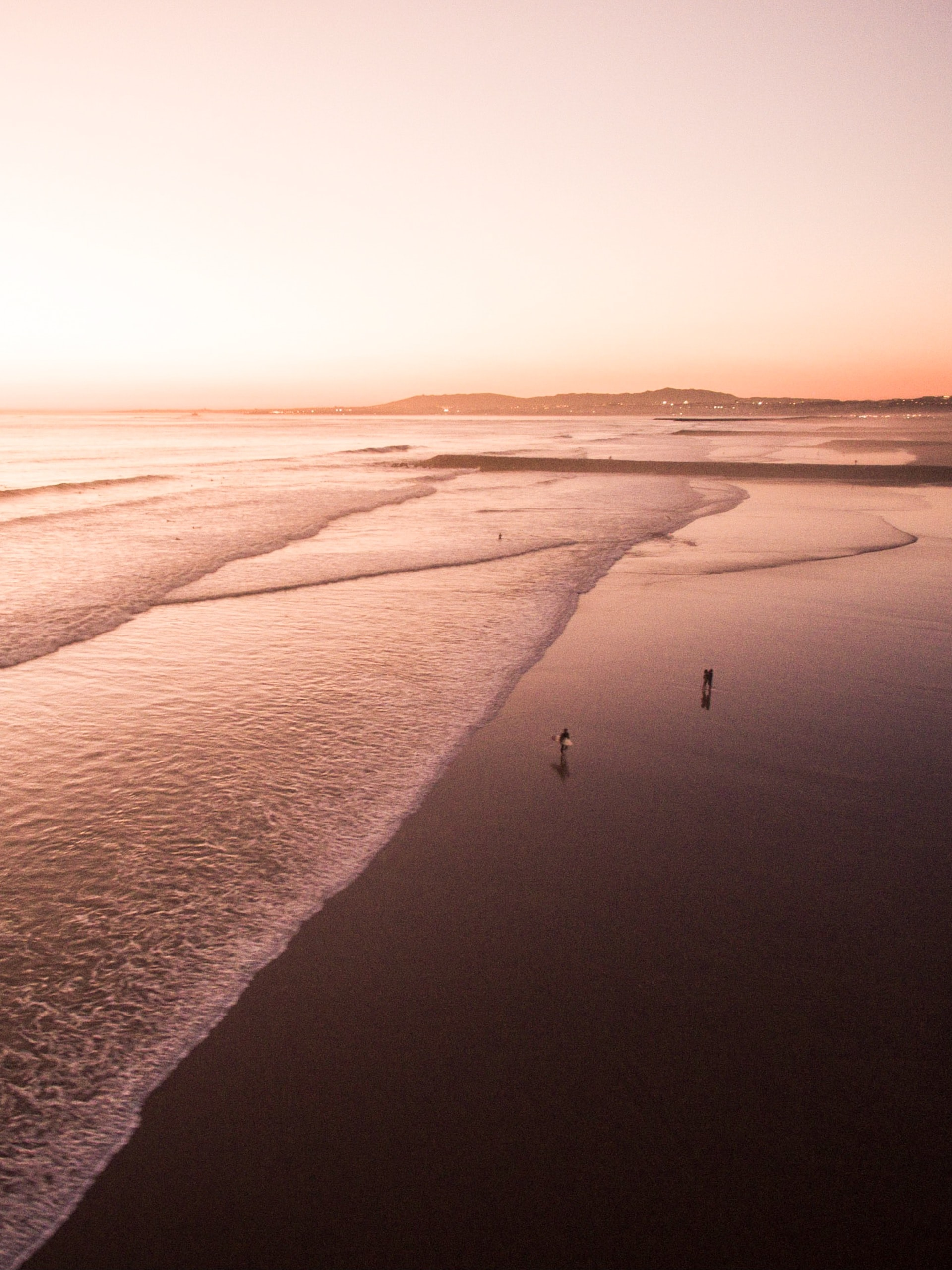 A few people and a surfer on a large beach.
