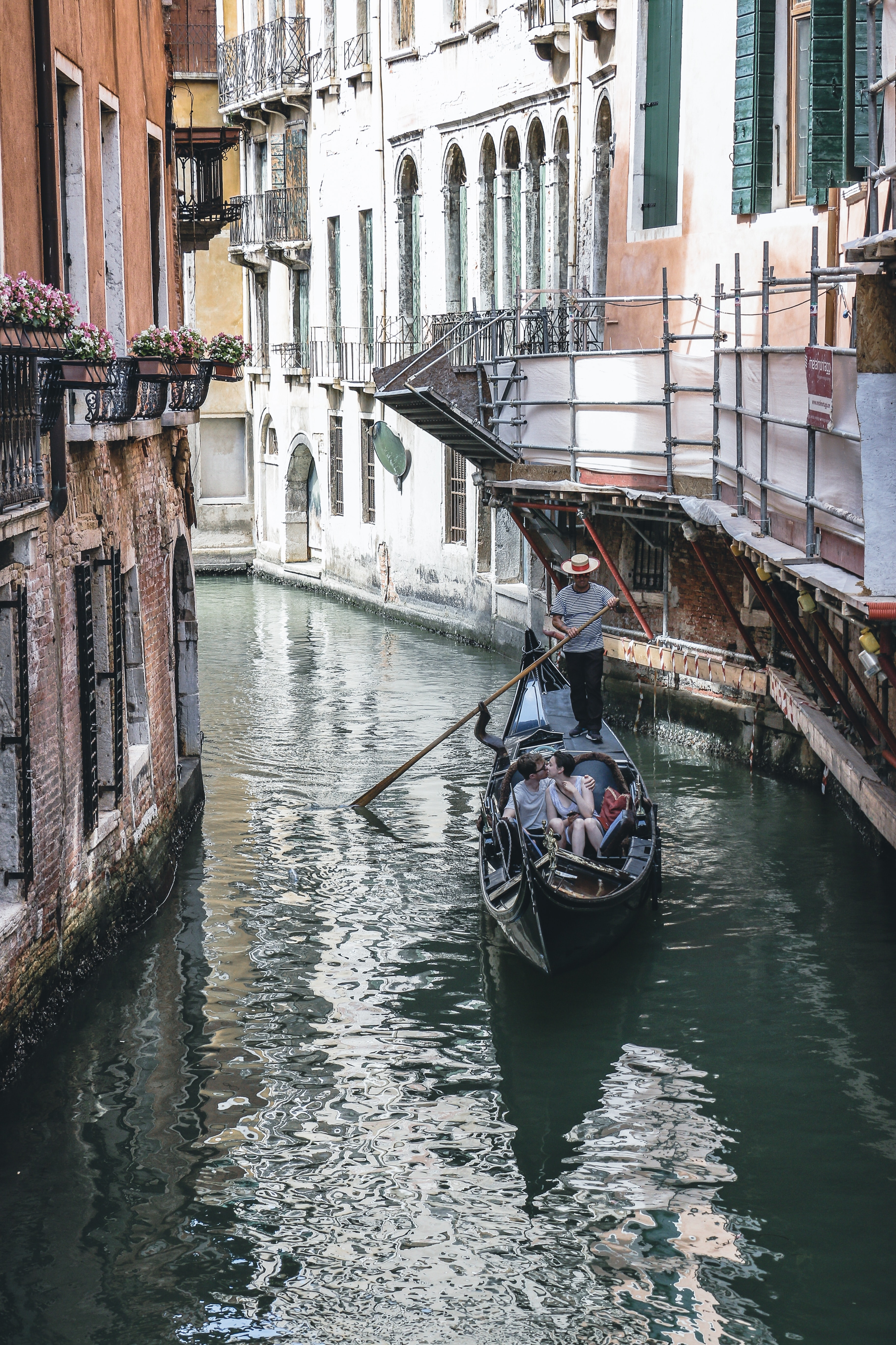 couple riding boat in Venice Canal at daytime
